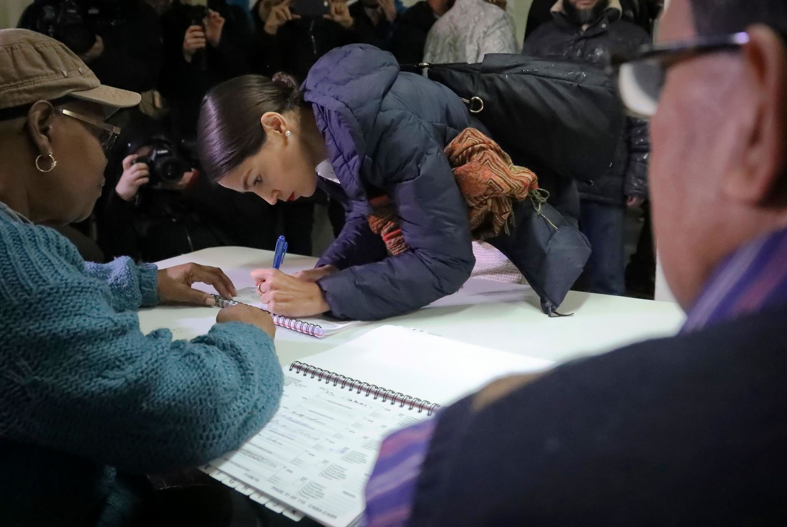 New York Democratic congressional candidate Alexandria Ocasio-Cortez, center, signs a register before voting, Tuesday Nov. 6, 2018, in the Parkchester community in the Bronx, N.Y. (AP Photo/Bebeto Matthews)