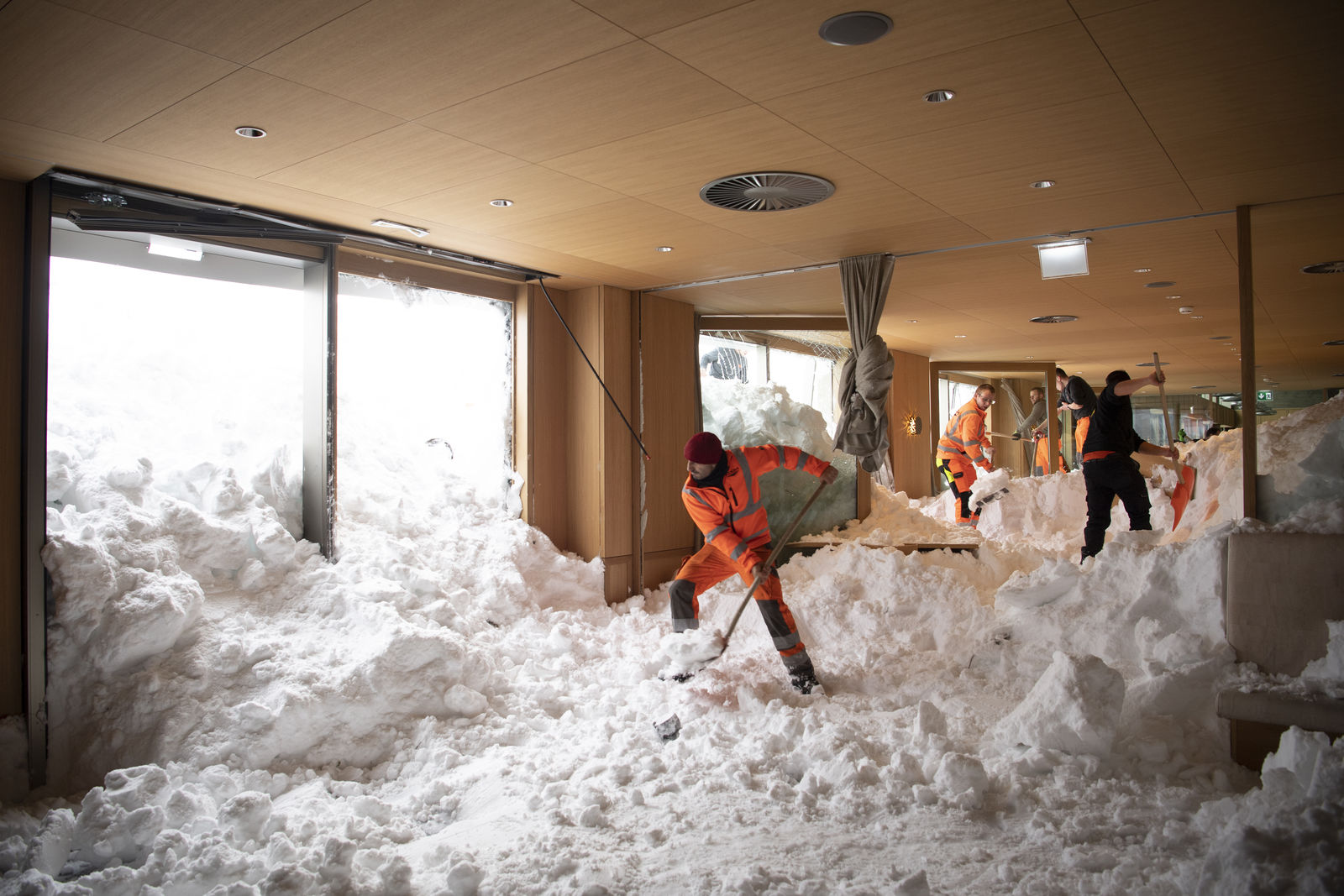People clear snow from inside the Hotel Saentis in Schwaegalp, Switzerland,, Switzerland, Friday Jan. 11. (Gian Ehrenzeller/Keystone via AP)