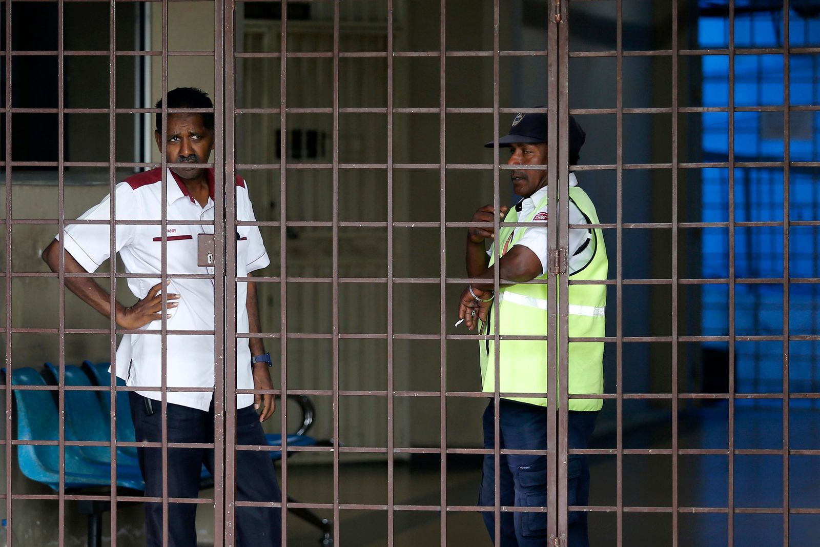 Security guards stand at the entrance to a hospital morgue in Seremban, Negeri Sembilan, Malaysia, Wednesday, Aug. 14, 2019. (AP Photo/Lai Seng Sin)