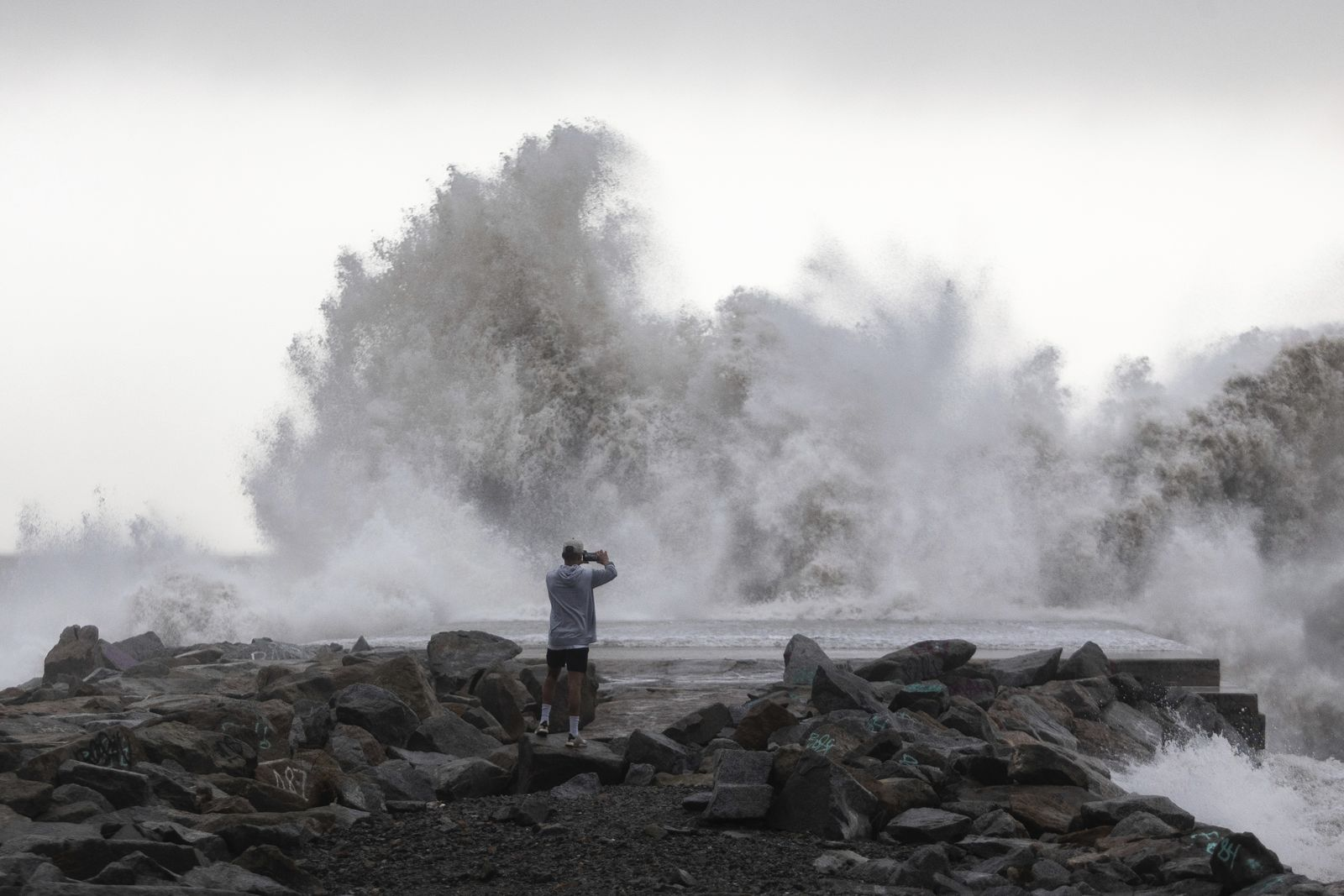 A man takes a snapshot of the waves hitting the breakwater in Barcelona, Spain, Wednesday, Jan. 22, 2020. Massive waves and gale-force winds smashed into seafront towns, damaging many shops and restaurants and flooding some streets. (AP Photo/Joan Mateu)