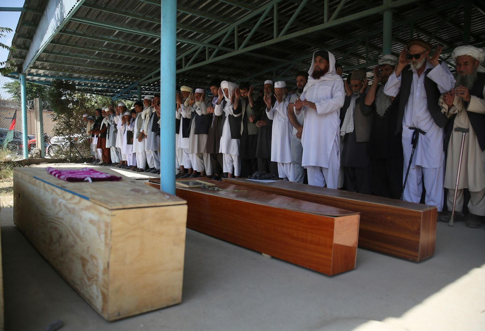 Afghans pray near the coffins of victims of the Dubai City wedding hall bombing during a mass funeral in Kabul, Afghanistan, Sunday, Aug.18, 2019.{ } (AP Photo/Rafiq Maqbool)