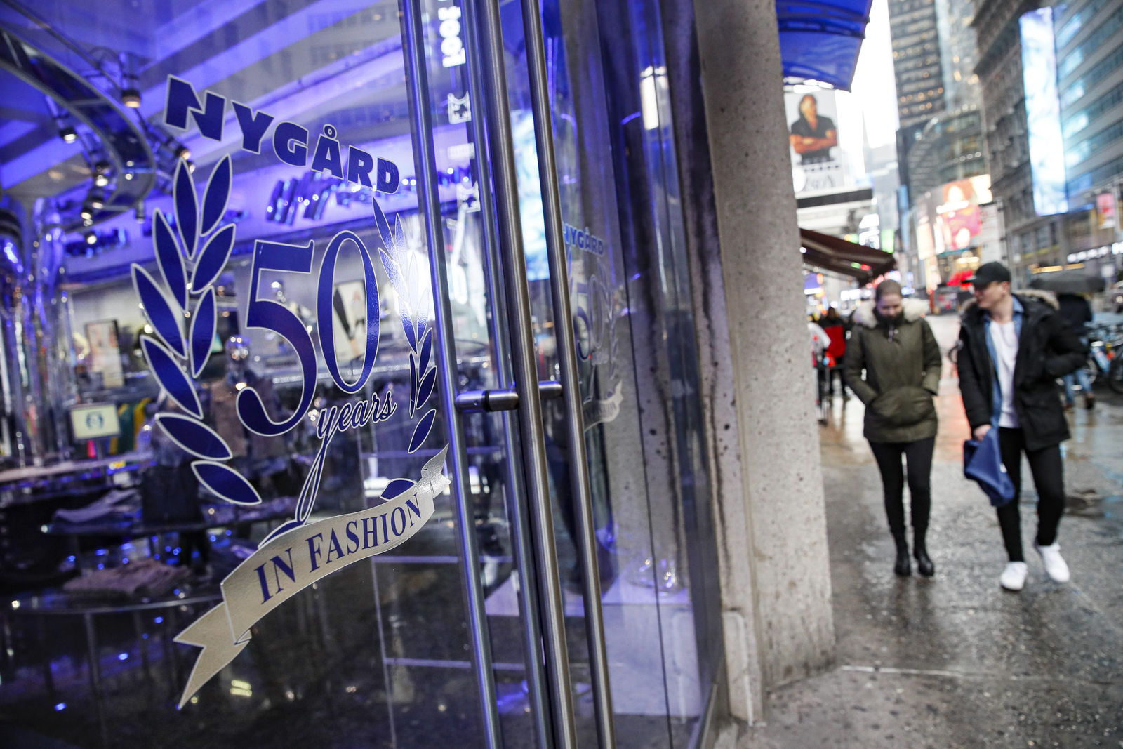 Pedestrians pass the storefront of Peter Nygard's Times Square headquarters, Tuesday, Feb. 25, 2020, in New York. Federal authorities on Tuesday, Feb. 25, 2020, raided the Manhattan headquarters of the Canadian fashion mogul Peter Nygard amid claims that he sexually assaulted and trafficked dozens of teenage girls and young women.   (AP Photo/John Minchillo)