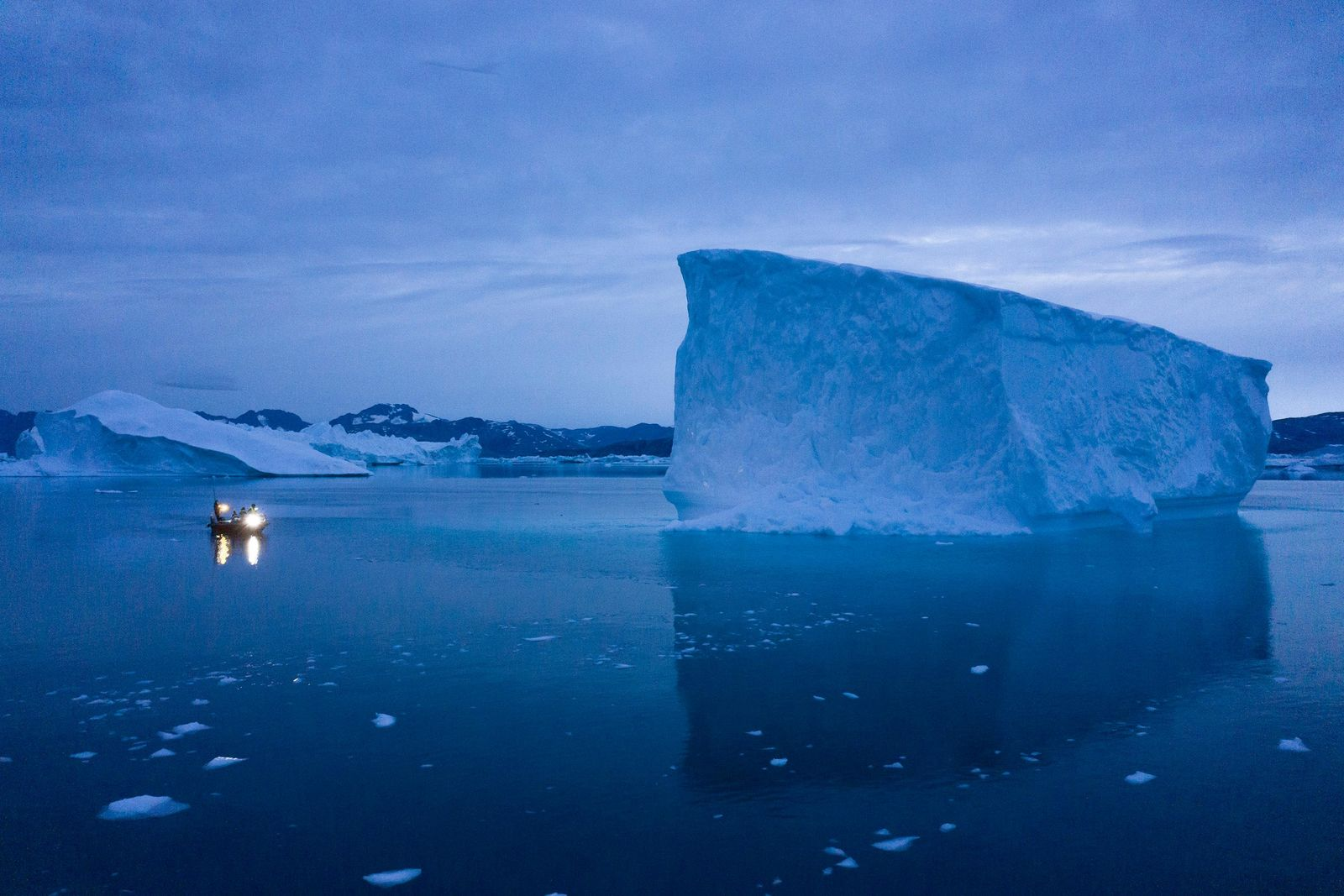 In this Aug. 15, 2019, photo, a boat navigates at night next to large icebergs in eastern Greenland.{ } (AP Photo/Felipe Dana)