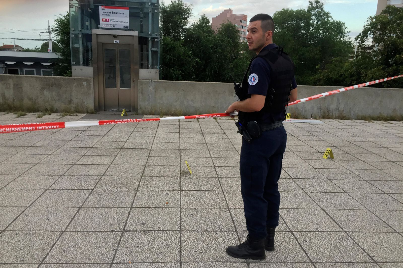 A police officer stands next to the place where an assailant stabbed one person to death and injured nine others has been arrested, Saturday Aug.31, 2019 just outside a subway station in Villeurbanne, outside Lyon, central France. The reason for the attack is unclear. (AP Photo/Nicolas Vaux-Montagny)