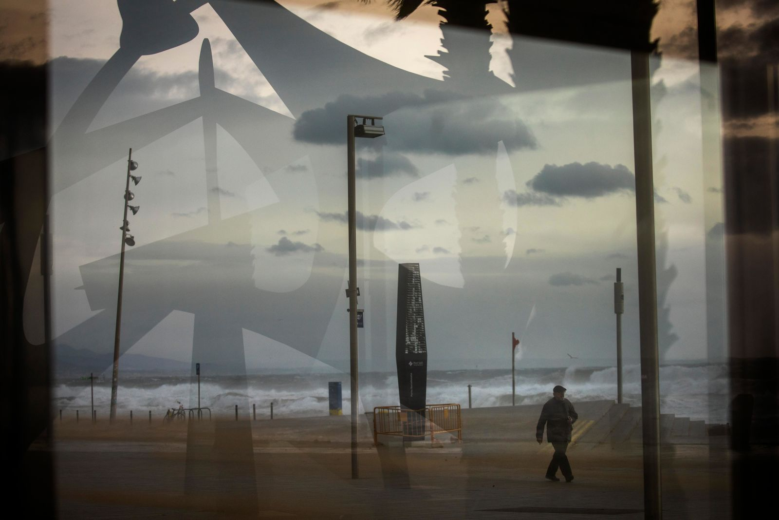 A man is seen through a window as he walks near the beach during strong winds in Barcelona, Spain, Monday, Jan. 20, 2020. (AP Photo/Emilio Morenatti)