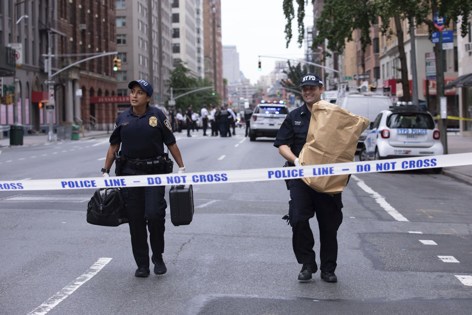 An investigator carries away a suspicious package as evidence after it was thought to be an explosive device in Manhattan's Chelsea neighborhood Friday, Aug. 16, 2019, in New York. The scare happened about two hours after two abandoned objects that looked like pressure cookers prompted an evacuation of a major transit hub in lower Manhattan. The police bomb squad later determined they were not explosives. (AP Photo/Kevin Hagen).