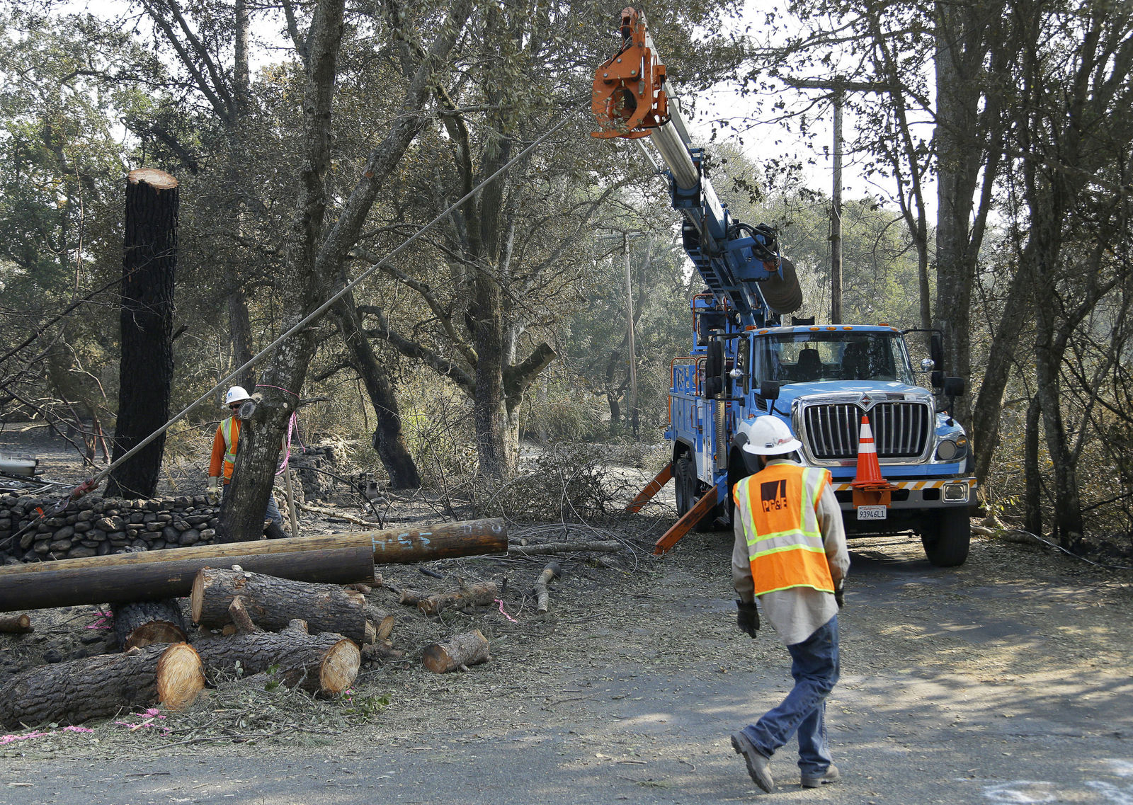 FILE - In this Oct. 18, 2017 file photo, a Pacific Gas & Electric crew works on replacing poles destroyed by wildfires in Glen Ellen, Calif. A U.S. judge in San Francisco overseeing a criminal case against Pacific Gas & Electric Co. is scaling back his proposals to prevent the utility's equipment from causing more wildfires. Judge William Alsup said in an order late Tuesday, March 5, 2019, that he's now considering making PG&E comply with targets in a wildfire mitigation plan that the company submitted to California regulators. (AP Photo/Ben Margot, File)