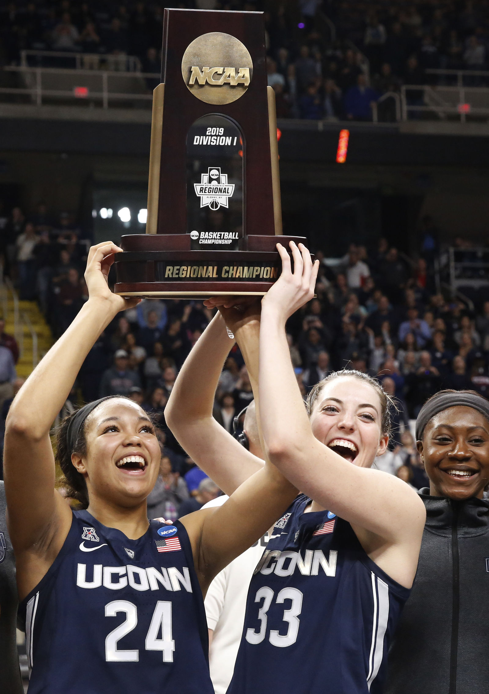 Connecticut forward Napheesa Collier (24) and guard Katie Lou Samuelson (33) hold up the trophy after defeating Louisville in a regional championship final in the NCAA women's college basketball tournament, Sunday, March 31, 2019, in Albany, N.Y. (AP Photo/Kathy Willens)