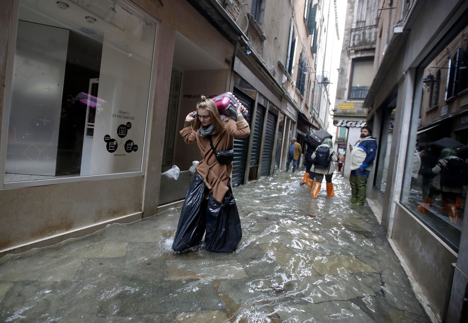 A woman wears bin bags as she carries her suitcase while wading through high water, in Venice, Wednesday, Nov. 13, 2019. (AP Photo/Luca Bruno)