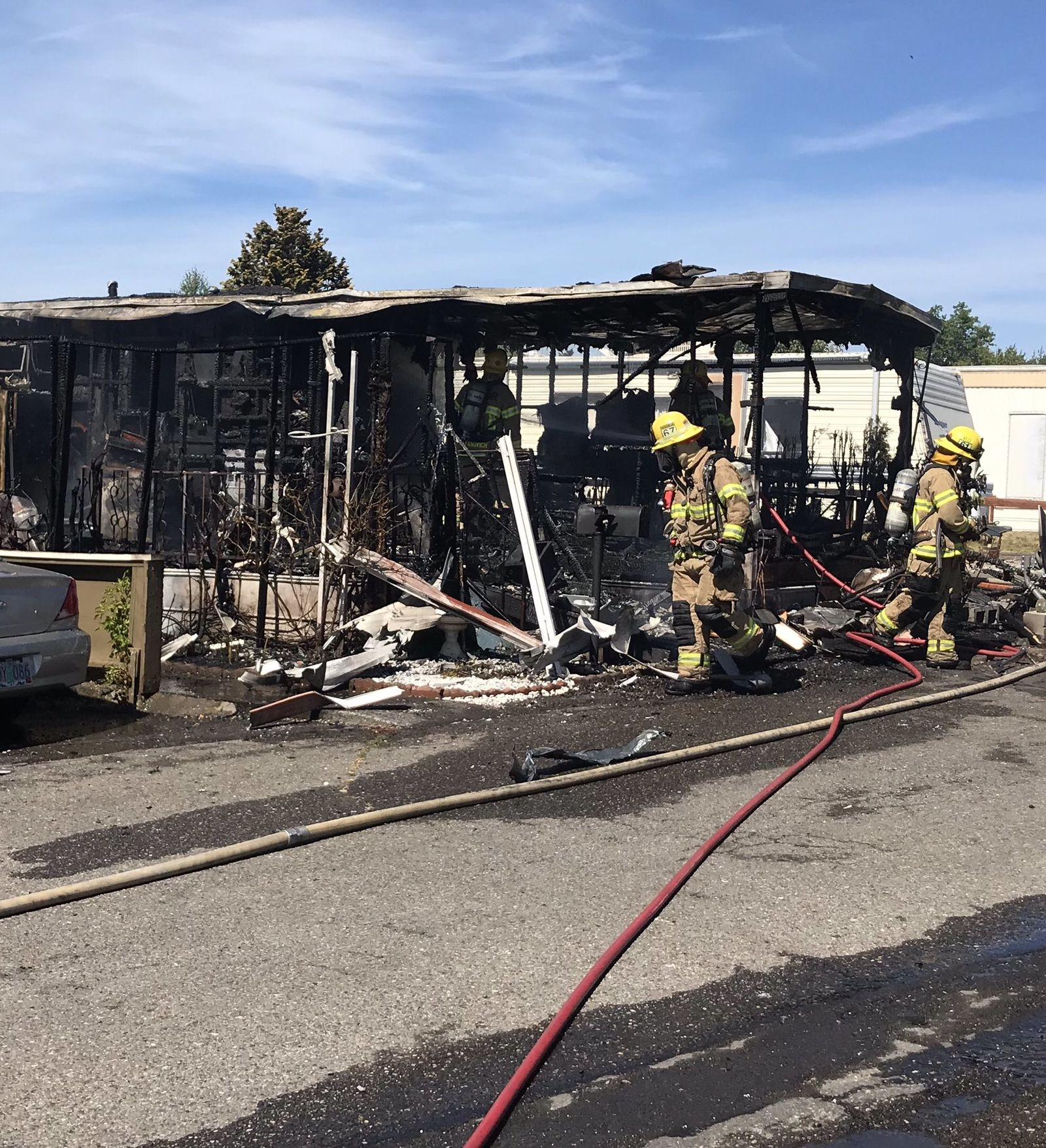 A fire crew works to clean up and put out hot spots in a fire that destroyed this mobile home in Beaverton Monday, June 17, 2019. (Photo: TVF&R){ }