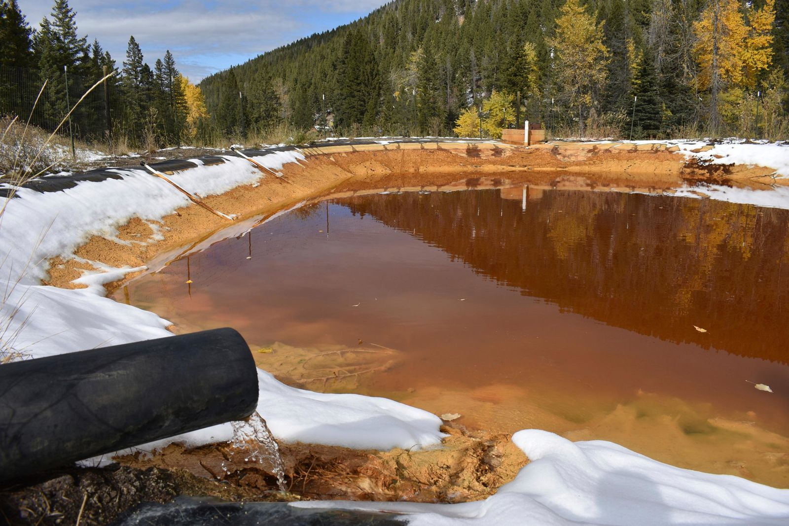 FILE - In this Oct. 12, 2018, file photo, water contaminated with arsenic, lead and zinc flows from a pipe out of the Lee Mountain mine and into a holding pond near Rimini, Mont. . (AP Photo/Matthew Brown, File)