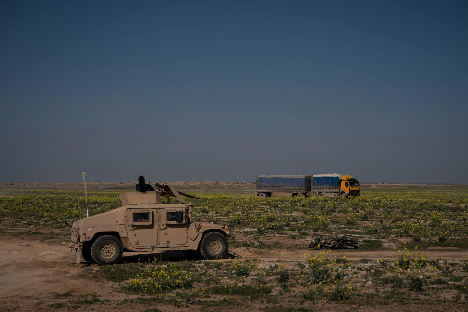 A U.S.-backed Syrian Democratic Forces (SDF) Humvee stands by as a truck that is part of a convoy evacuating hundreds out of the last territory held by Islamic State militants, passes in Baghouz, eastern Syria, Wednesday, Feb. 20, 2019. The evacuation signals the end of a week long standoff and opens the way to U.S.-backed Syrian Democratic Forces (SDF) recapture the territory. (AP Photo/Felipe Dana)