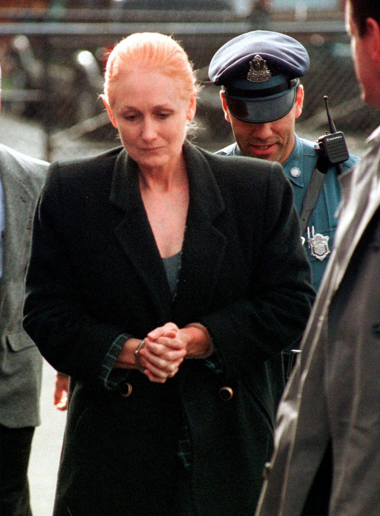 "FILE - In this Nov. 8, 1999 file photo, Margaret Rudin is escorted by police into Framingham District Court in Framingham, Mass., before her arraignment on charges in connection with the shooting death of her husband. On Friday, Jan. 10, 2020, Rudin was released from prison, more than 25 years after her millionaire husband's burned body was found outside Las Vegas and 20 years after a tip generated by a ""most wanted"" TV show led to her arrest while living in Massachusetts with a retired firefighter she met in Mexico. (AP Photo/Michael Dwyer, File)"