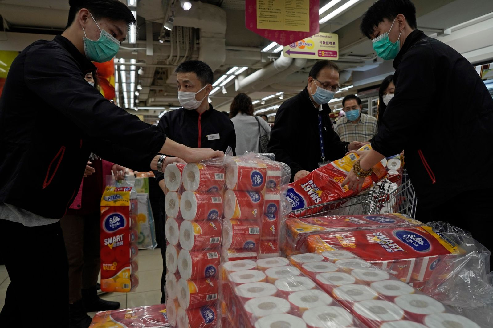 Customers queue to buy supplies of toilet paper in a supermarket in Hong Kong, Friday, Feb. 14, 2020. China on Friday reported another sharp rise in the number of people infected with a new virus, as the death toll neared 1,400. (AP Photo/Kin Cheung)