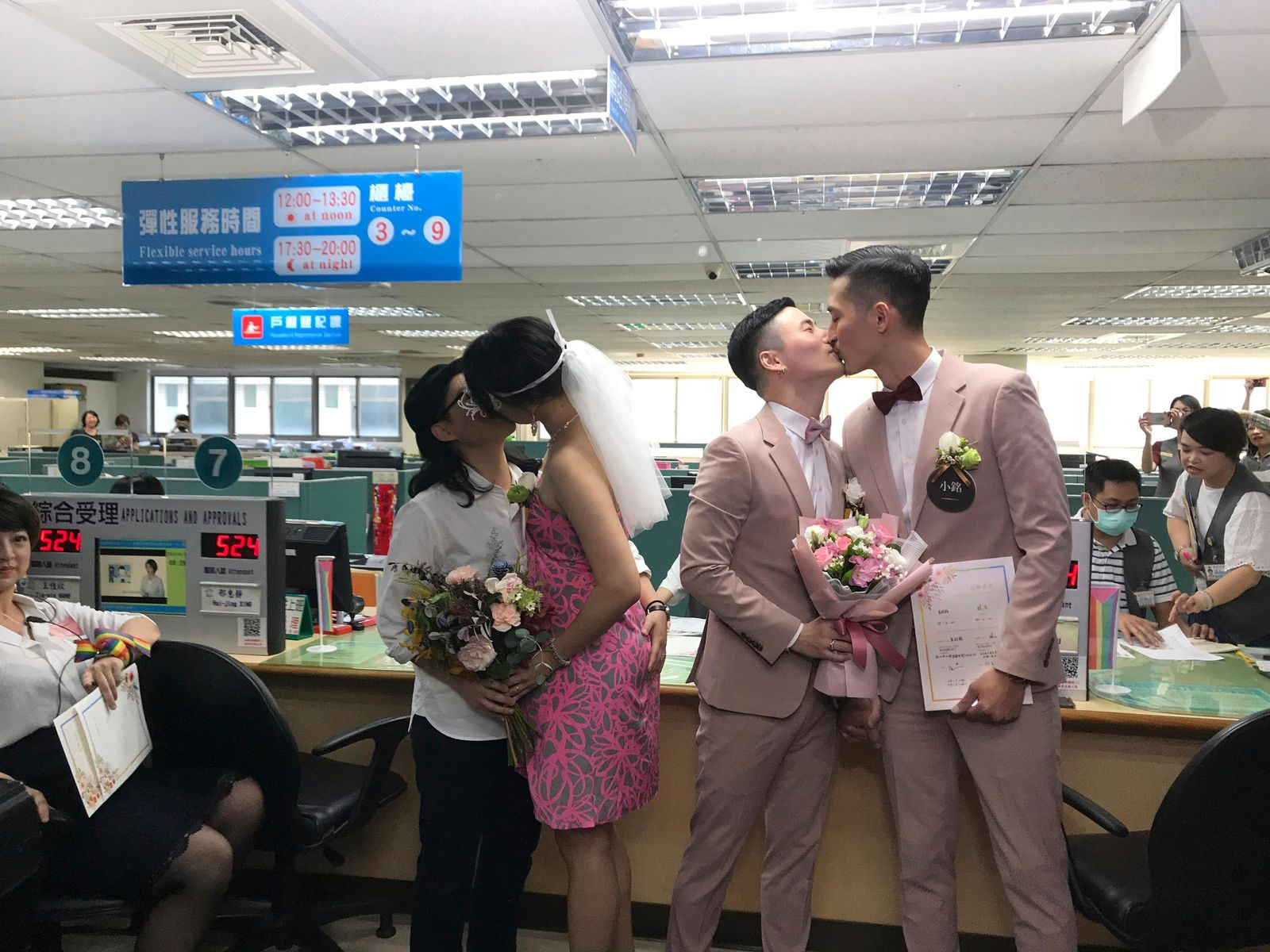 Two same-sex couple seal their legal marriages with a kiss at the registration office in Xingyi District in Taipei, Taiwan, Friday, May 24, 2019. Hundreds of same-sex couples in Taiwan are rushing to the household registration office on the first day that a landmark decision to legalize same-sex marriage has taken effect. (AP Photo/Johnson Lai)