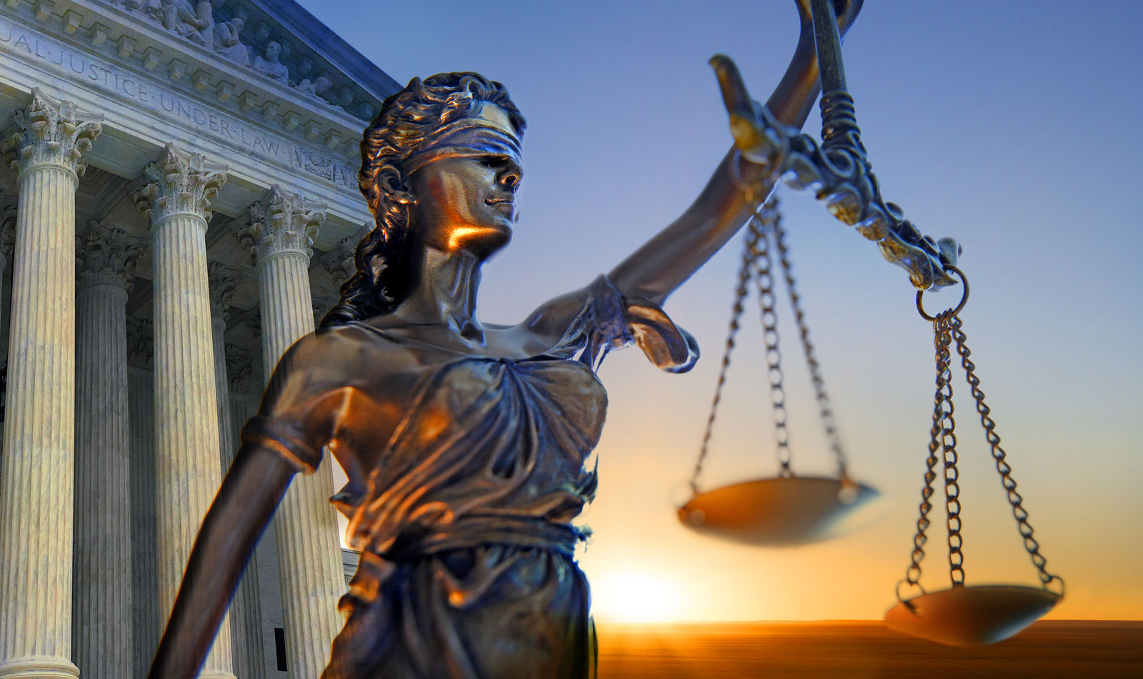 A statue of the blindfolded lady justice in front of the United States Supreme Court building as the sun rises in the distance symbolizing the dawning of a new era. (Getty Images)