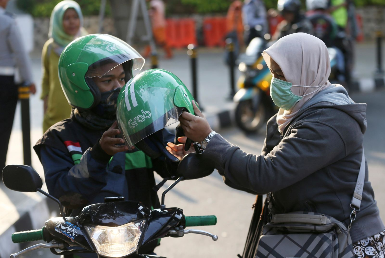 A Grab driver passes a helmet to a passenger in Jakarta, Indonesia, Monday, July 29, 2019. Japanese technology company Softbank and Southeast Asian ride hailing app Grab said Monday, July 29, 2019, they're investing $2 billion in Indonesia over the next five years. (AP Photo/Achmad Ibrahim)