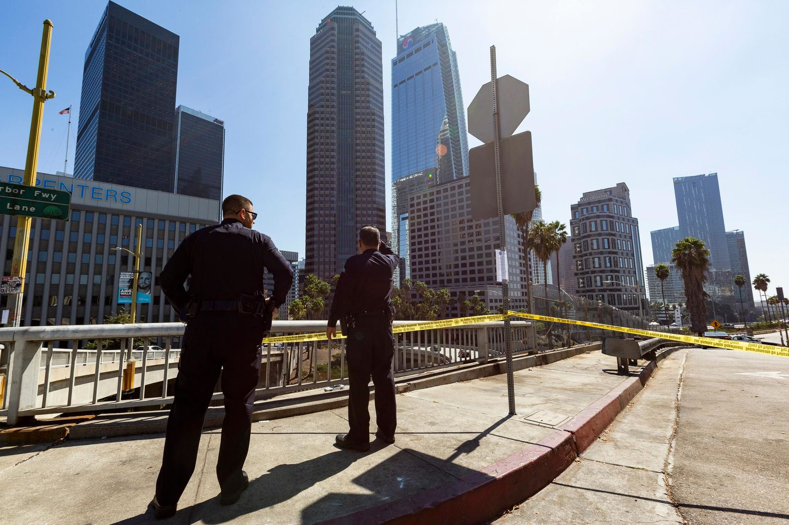 Los Angeles Police officers watch over a closed street parallel to the Harbor Freeway ramp, during the visit of President Donald