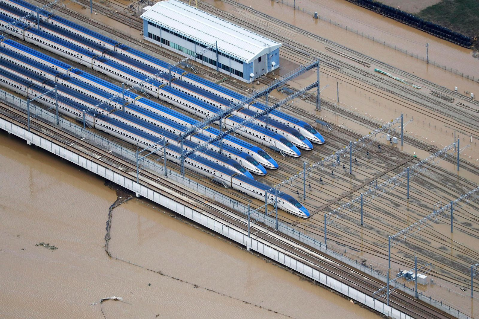 Bullet trains sit at their base as the surrounding land is still flooded following Typhoon Hagibis, in Nagano, central Japan Monday, Oct. 14, 2019. Rescue crews in Japan dug through mudslides and searched near swollen rivers Monday as they looked for those missing from the typhoon that  caused serious damage in central and northern Japan. (Kyodo News via AP)