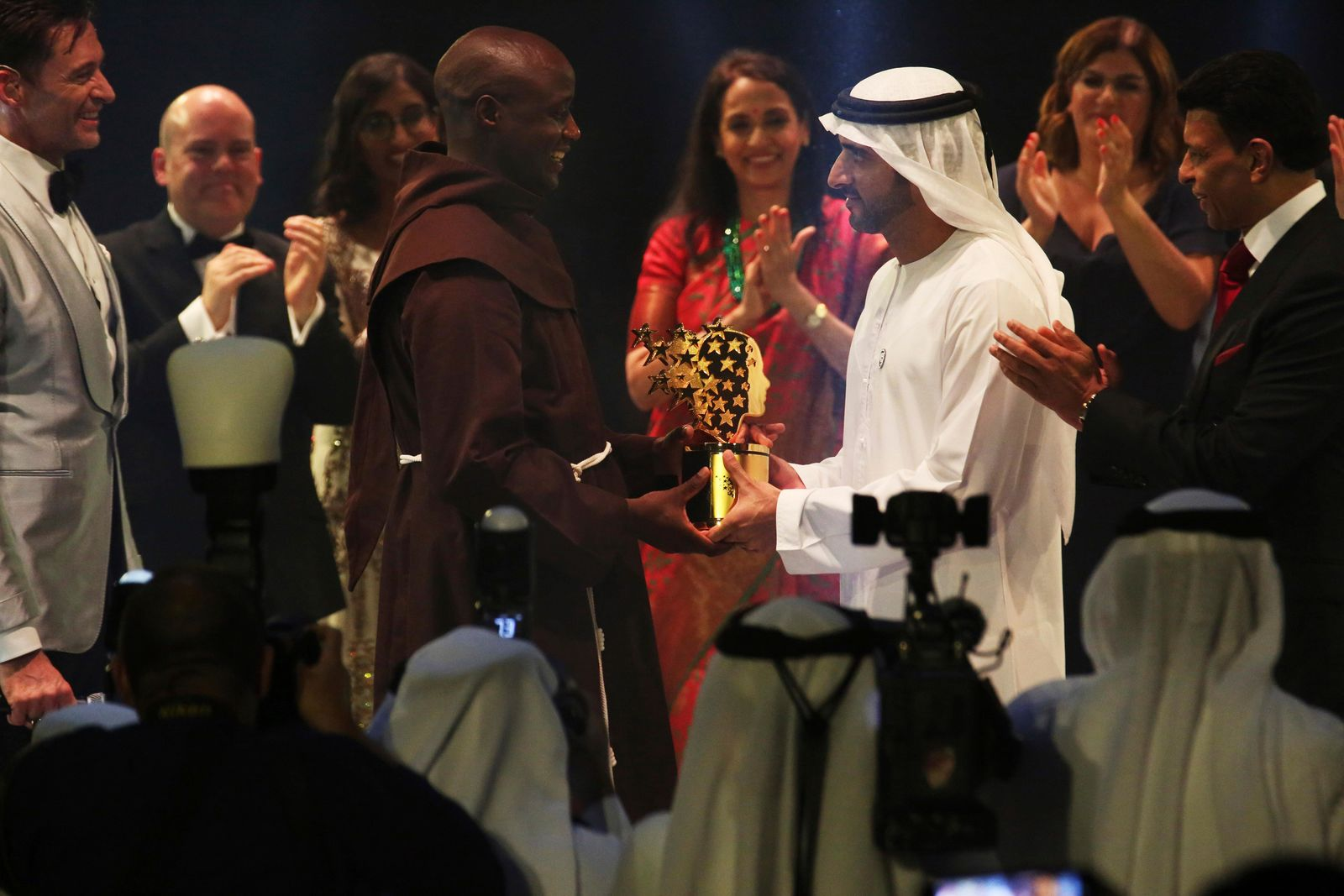 Kenyan teacher Peter Tabichi, center left, receives a statue from Dubai crown prince Sheikh Hamdan bin Mohammed Al Maktoum, center right, after winning the $1 million Global Teacher Prize in Dubai, United Arab Emirates, Sunday, March 24, 2019. (AP Photo/Jon Gambrell)