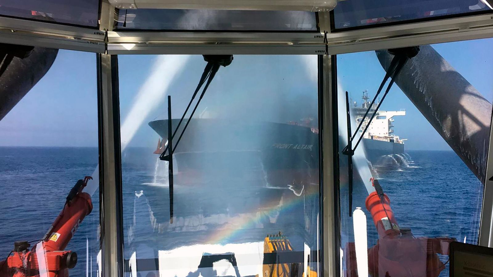 In this photo dated Thursday June 13, 2019, made available by the Norwegian shipowner Frontline, showing the crude oil tanker Front Altair seen through glass observation window as water cannon operate during the firefighting of the fire onboard the Norwegian ship in the Gulf of Oman.  The U.S. Navy rushed to assist the stricken vessels in the Gulf of Oman, off the coast of Iran, as two oil tankers came under suspected attack amid heightened tension between Iran and the U.S. (Frontline via AP)