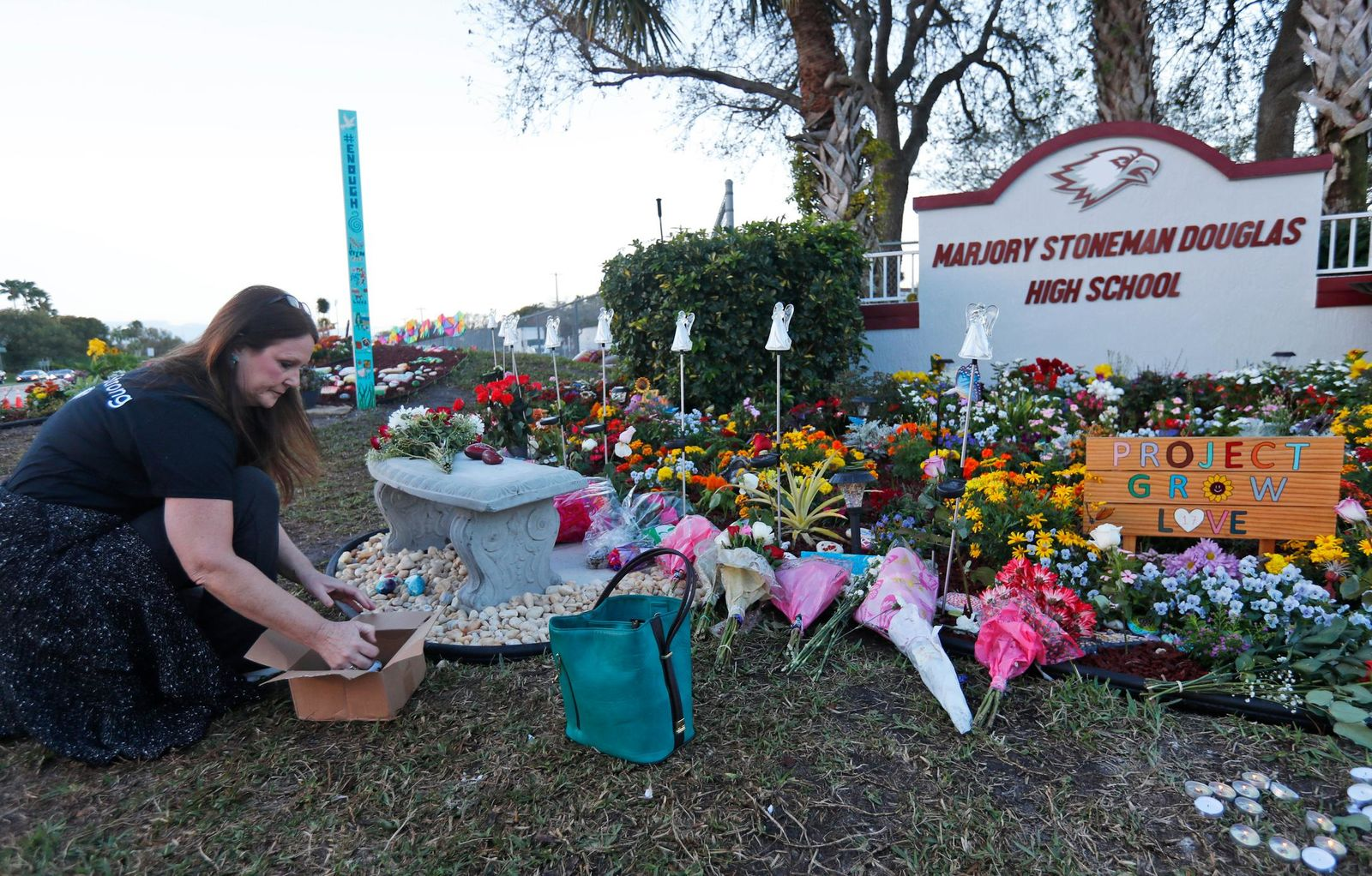 Suzanne Devine Clark, an art teacher at Deerfield Beach Elementary School, places painted stones at a memorial outside Marjory Stoneman Douglas High School during the one-year anniversary of the school shooting, Thursday, Feb. 14, 2019, in Parkland, Fla. A year ago on Thursday, 14 s