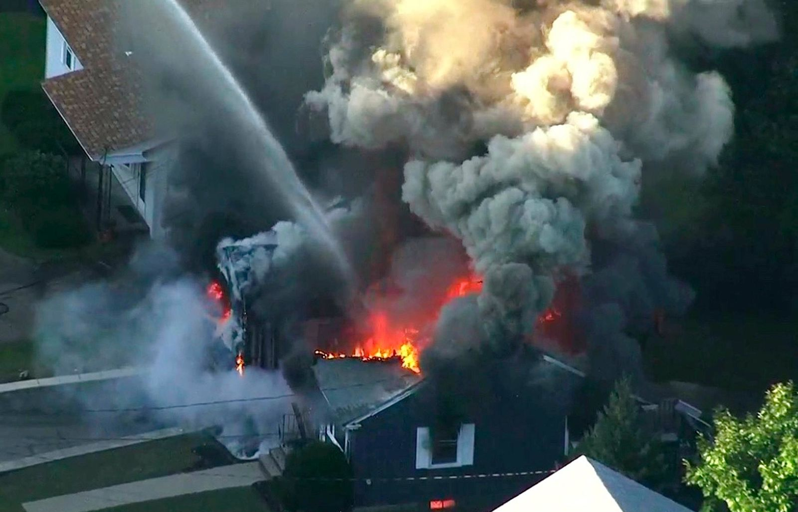 FILE - In this Sept. 13, 2018 file image from video provided by WCVB in Boston, flames consume the roof of a home following an explosion in Lawrence, Mass.{ } (WCVB via AP, File)