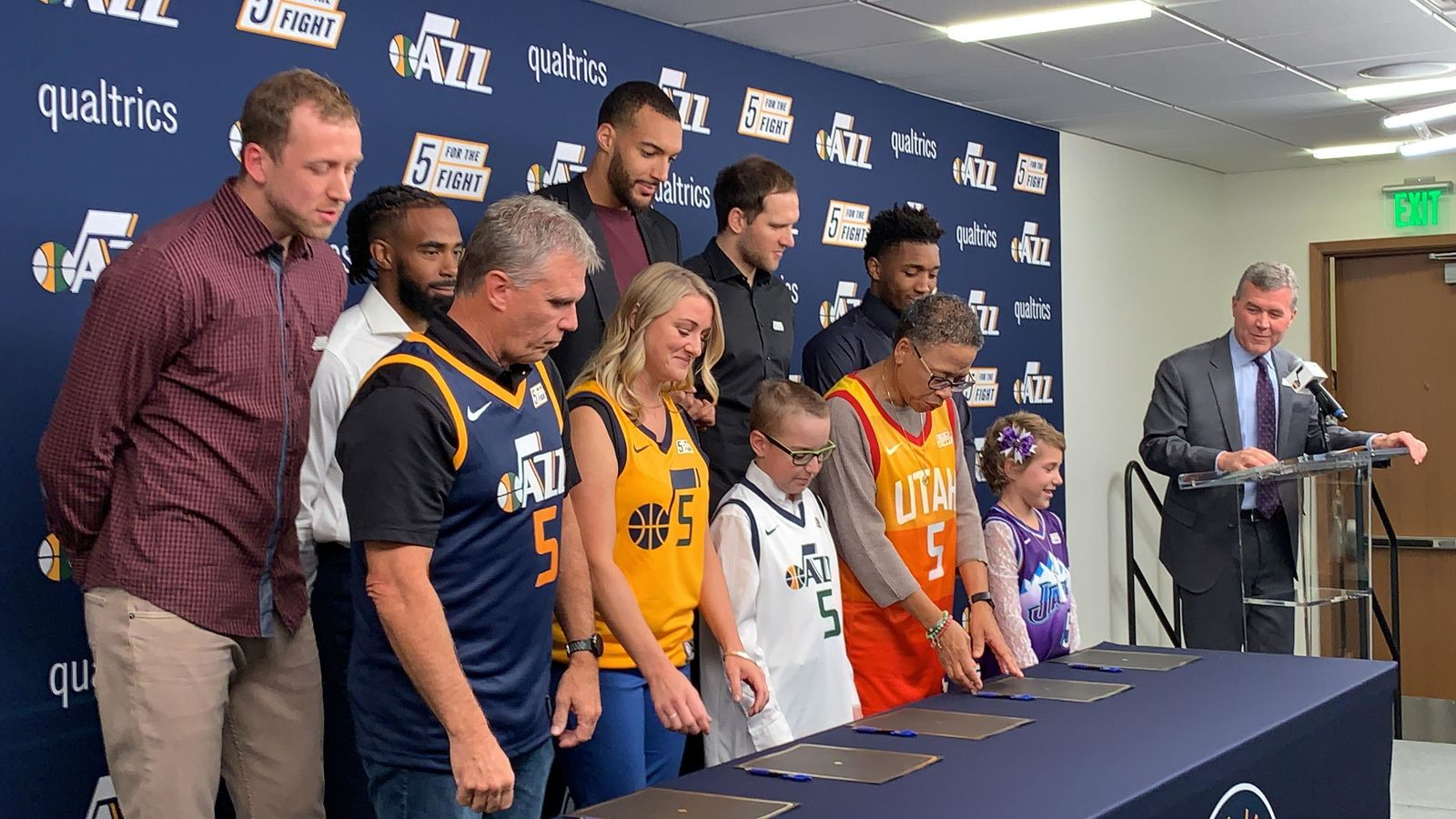 "Everyone poses for a photo op promoting ""5 For The Fight"" which aims to fund cancer research. (L-R) Joe Ingles (Jazz forward), Dave Warren (cancer fighter), Mike Conley (Jazz point guard), Dani Phillips (cancer fighter), Rudy Gobert (2-time Defensive Player of the Year, Utah Jazz Center) with Wyatt Page (young cancer fighter), Emma Houston (cancer fighter), Bojan Bogdanovic (Utah Jazz forward), Donovan ""Spida"" Mitchell (Utah Jazz guard) with Baylee Semrow (young cancer fighter). (Photo: Adam Forgie, KUTV)"