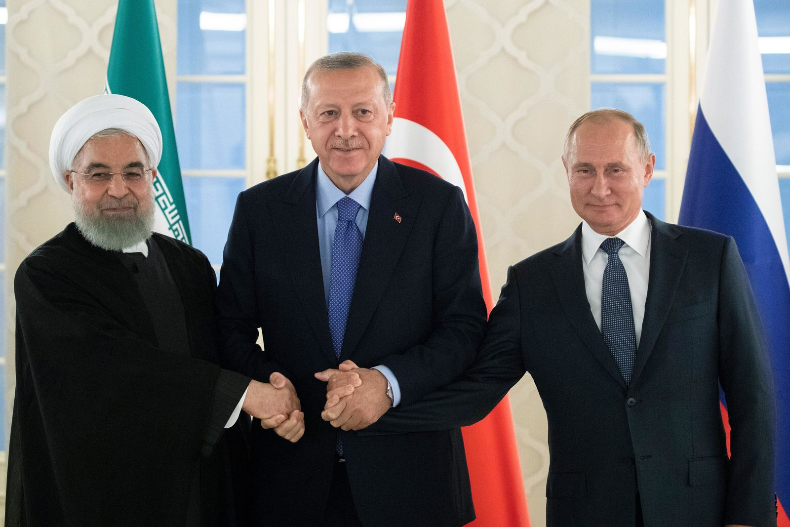 FILE - This Sept. 16, 2019 file photo, from left: Iranian President Hassan Rouhani, Turkish President Recep Tayyip Erdogan and Russian President Vladimir Putin shake hands during their meeting in Ankara, Turkey. America maintains some 1,000 troops in Syria who work alongside the Kurdish fighters. America's foes -- Assad, Russia, and Iran -- all stand to gain from a U.S. troop withdrawal in Syria and will likely bide their time until they can move in and retake the area. (AP Photo/Pavel Golovkin, Pool, File)