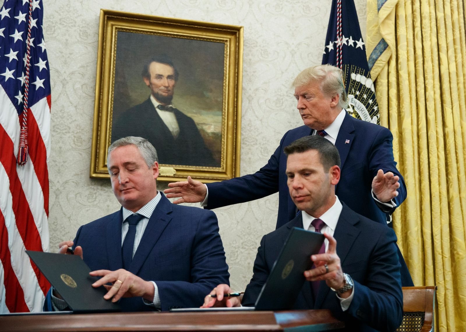 President Donald Trump, walks to acting Department of Homeland Security Secretary Kevin McAleenan, seated right, and Guatemalan Interior Minister Enrique Degenhart in the Oval Office of the White House in Washington. (AP Photo/Carolyn Kaster)