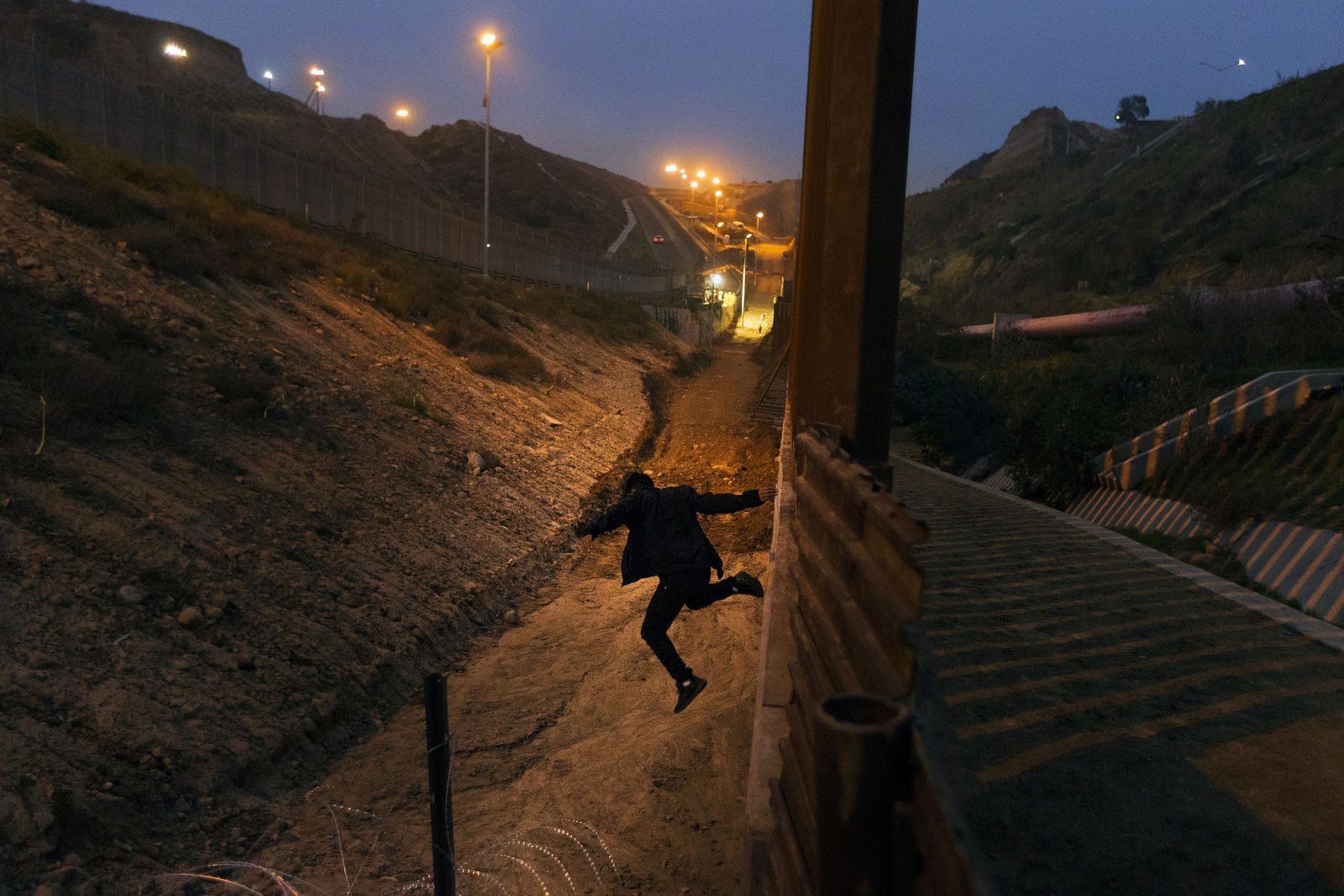 FILE - In this Dec. 21, 2018, file photo, a Honduran youth jumps from the U.S. border fence in Tijuana, Mexico.   California's attorney general filed a lawsuit Monday, Feb. 18, 2019, against President Donald Trump's emergency declaration to fund a wall on the U.S.-Mexico border.{ } (AP Photo/Daniel Ochoa de Olza, File)
