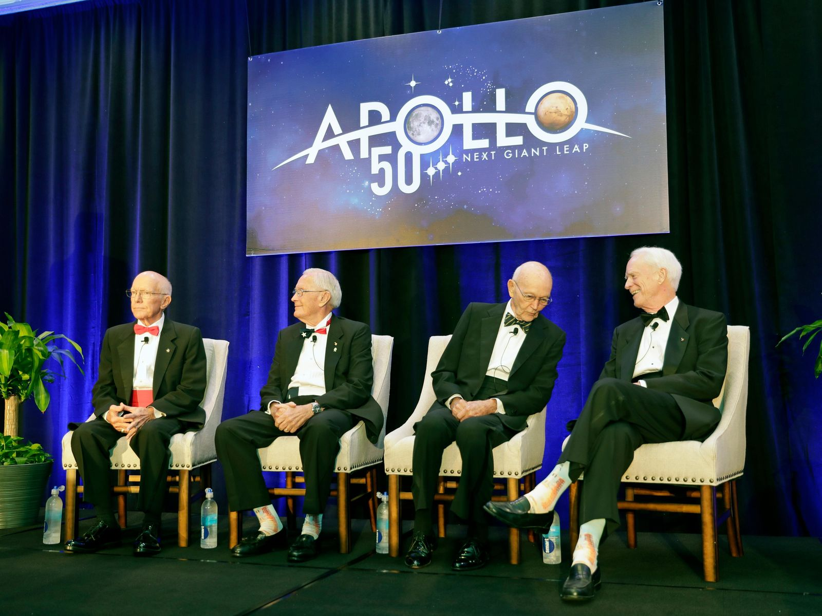 Apollo Legends attend a news conference from left, Gerry Griffin, Apollo flight director, and Charlie Duke, Apollo 16 astronaut, take their seats as Mike Collins, Apollo 11 astronaut admires Apollo 9 astronaut Rusty Schweickart's socks featuring a Saturn V rocket, during a news conference Tuesday, July 16, 2019, in Cocoa Beach, Fla. (AP Photo/John Raoux)