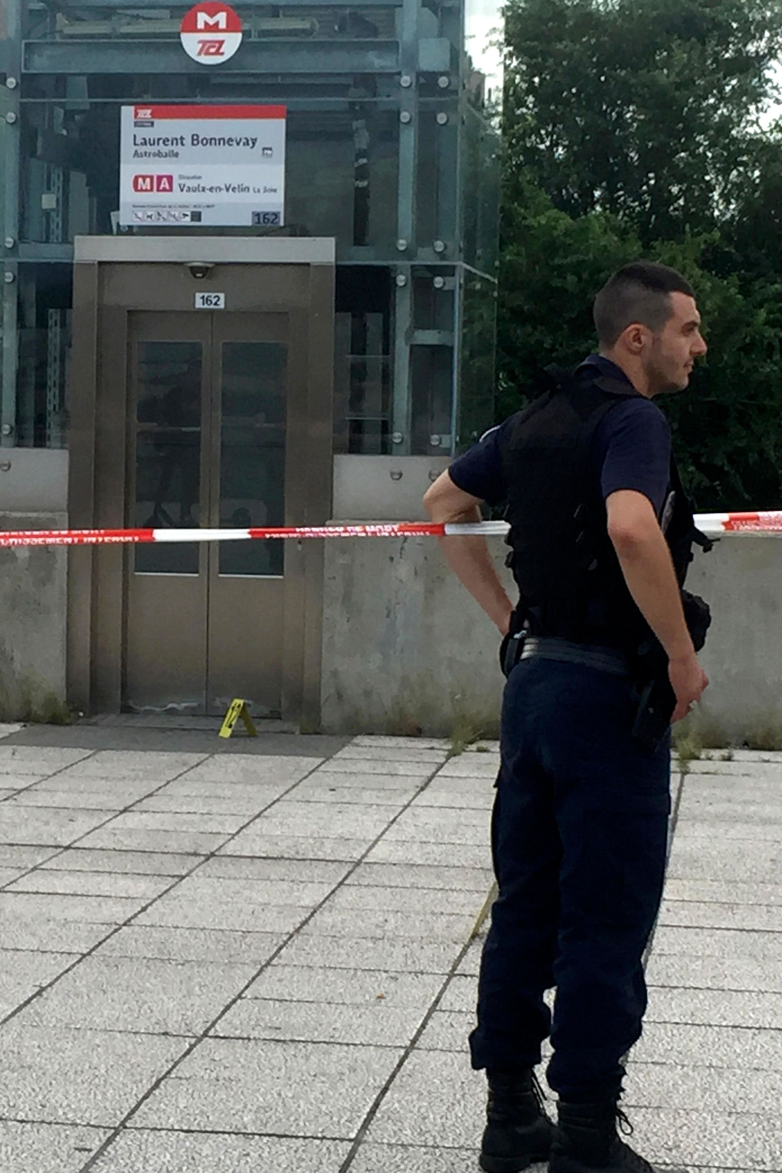 A police officer stands next to the place where an assailant who stabbed one person to death and injured nine others has been arrested, Saturday Aug.31, 2019 just outside a subway station in Villeurbanne, outside Lyon, central France. The reason for the attack is unclear. (AP Photo/Nicolas Vaux-Montagny)