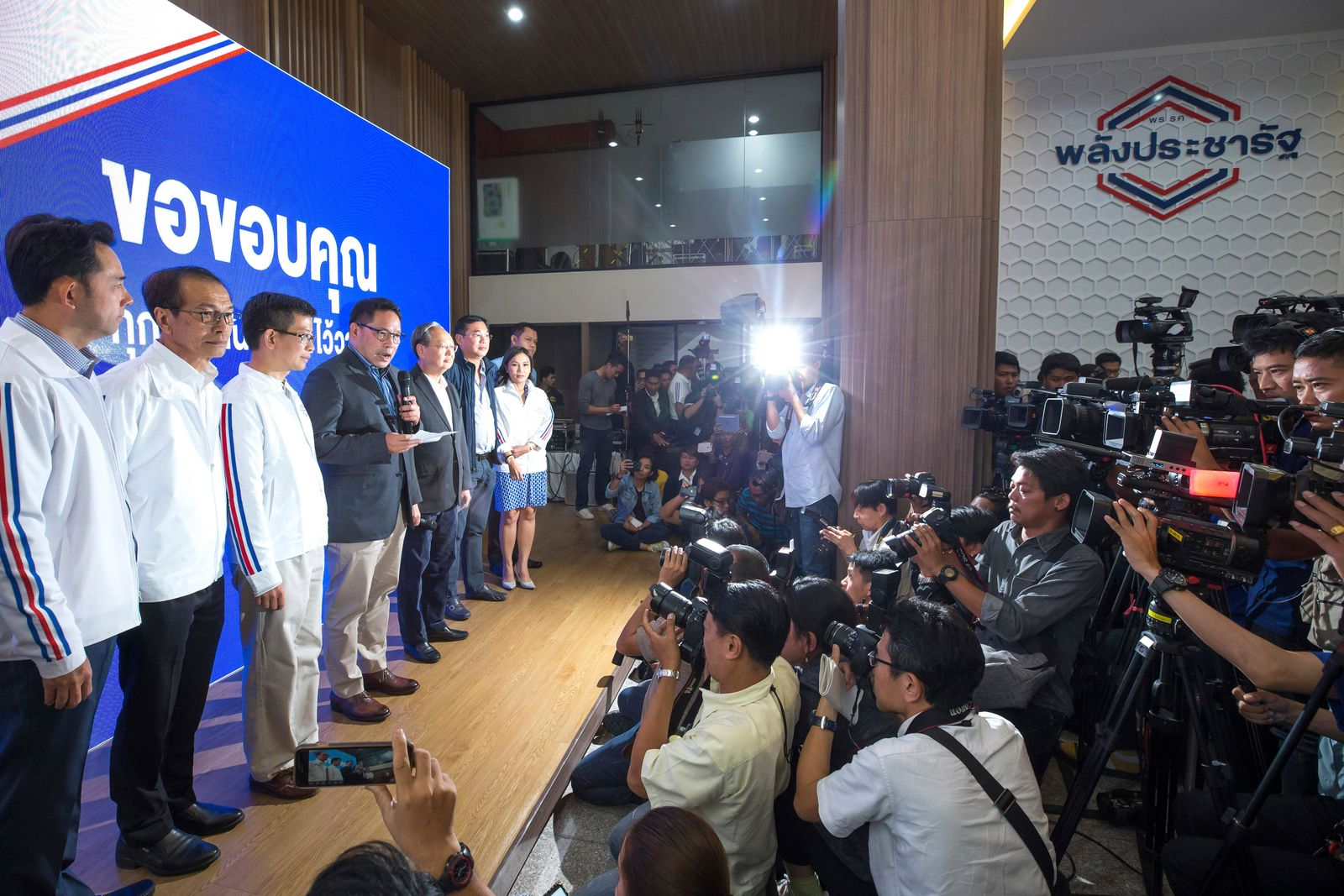 Thailand's Palang Pracharat Party leader Uttama Savanayana, center with a microphone in his hand speaks during a press conference in Bangkok, Thailand, Monday, March 25, 2019. The Election Commission announced the results of 350 constituency races but full vote counts, which are needed to determine the allocation of 150 other seats in the House of Representatives, won't be available until Friday. (AP Photo/Wason Wanichakorn)