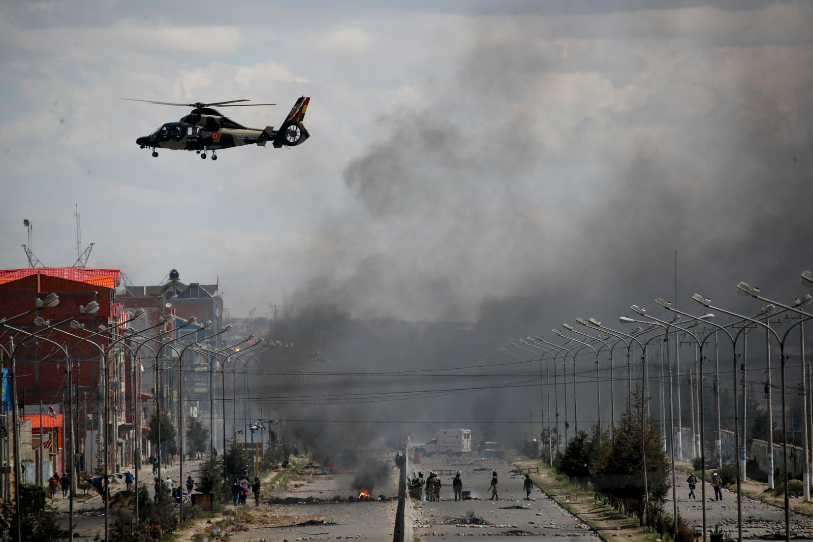 An Army helicopter flies over the road leading to the state-own Senkata filling gas plant in El Alto, on the outskirts of La Paz, Bolivia, as supporters of former President Evo Morales set up barricades, Tuesday, Nov. 19, 2019. (AP Photo/Natacha Pisarenko)