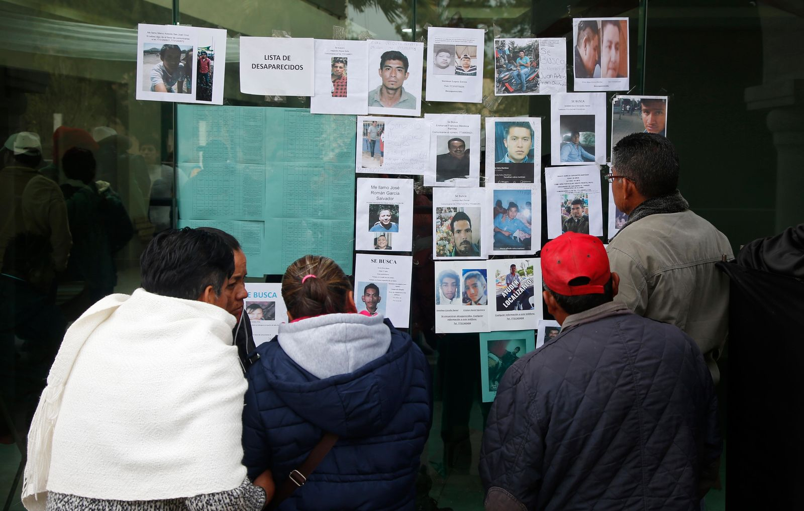 People look at photographs of people who are missing since the pipeline accident in Tlahuelilpan, Mexico, Sunday Jan. 20, 2019. A massive fireball that engulfed locals scooping up fuel spilling from a pipeline ruptured by thieves in central Mexico killed dozens of people and badly burned dozens more on Jan. 18. (AP Photo/Claudio Cruz)