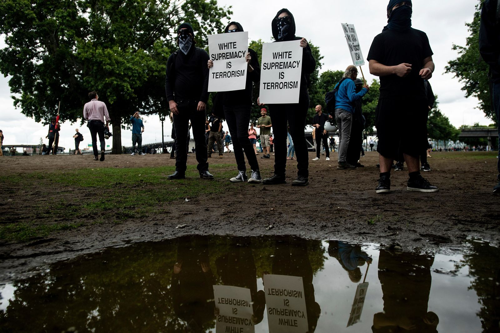 "Black-clad protesters, gathered to oppose conservative groups staging an ""End Domestic Terrorism"" rally, hold signs in Portland, Ore., on Saturday, Aug. 17, 2019. Police have mobilized to prevent clashes between conservative groups and counter-protesters who plan to converge in the city. (AP Photo/Noah Berger)"