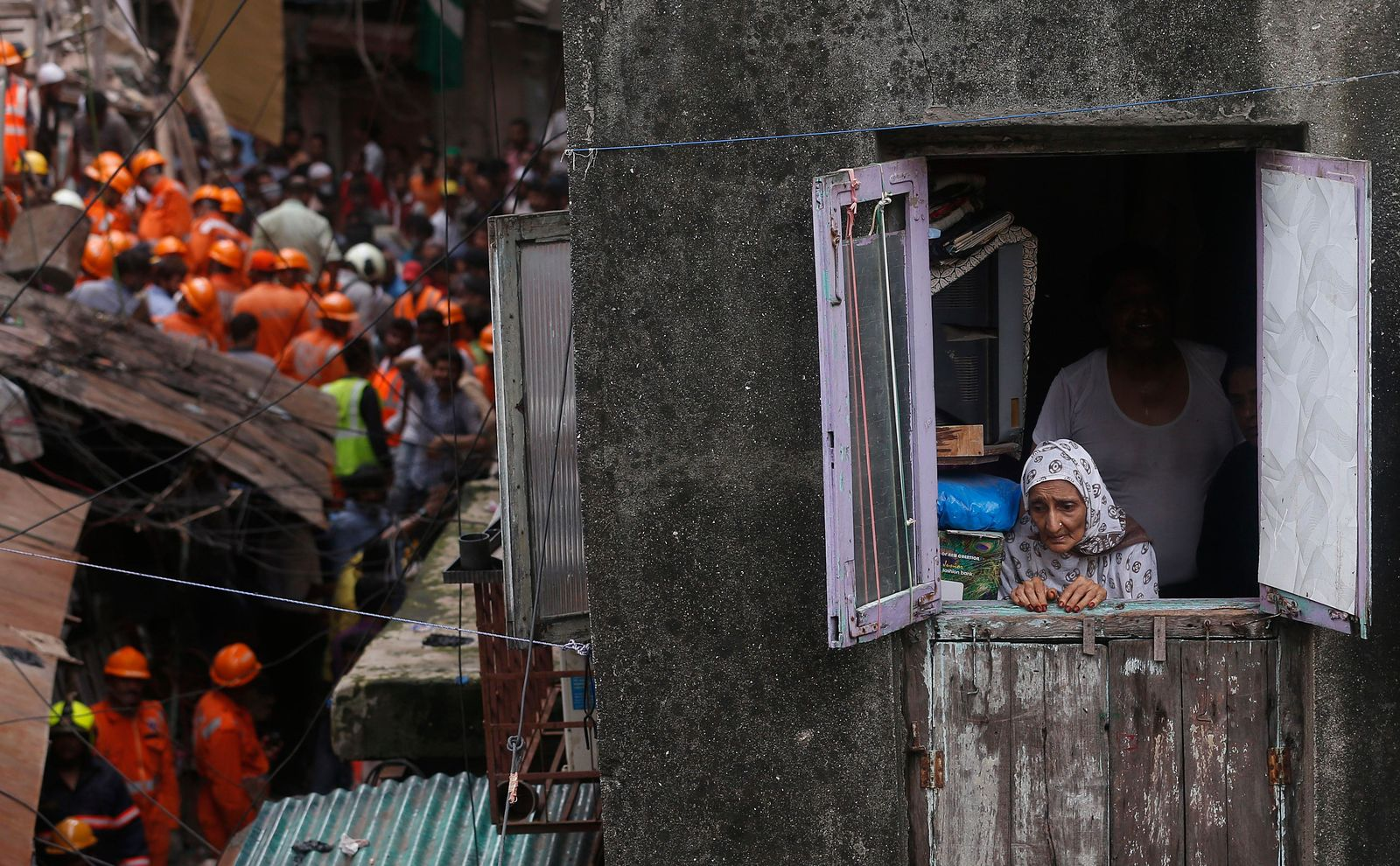 A woman looks from a window as rescuers work at the site of a building that collapsed in Mumbai, India, Tuesday, July 16, 2019 (AP Photo/Rafiq Maqbool)