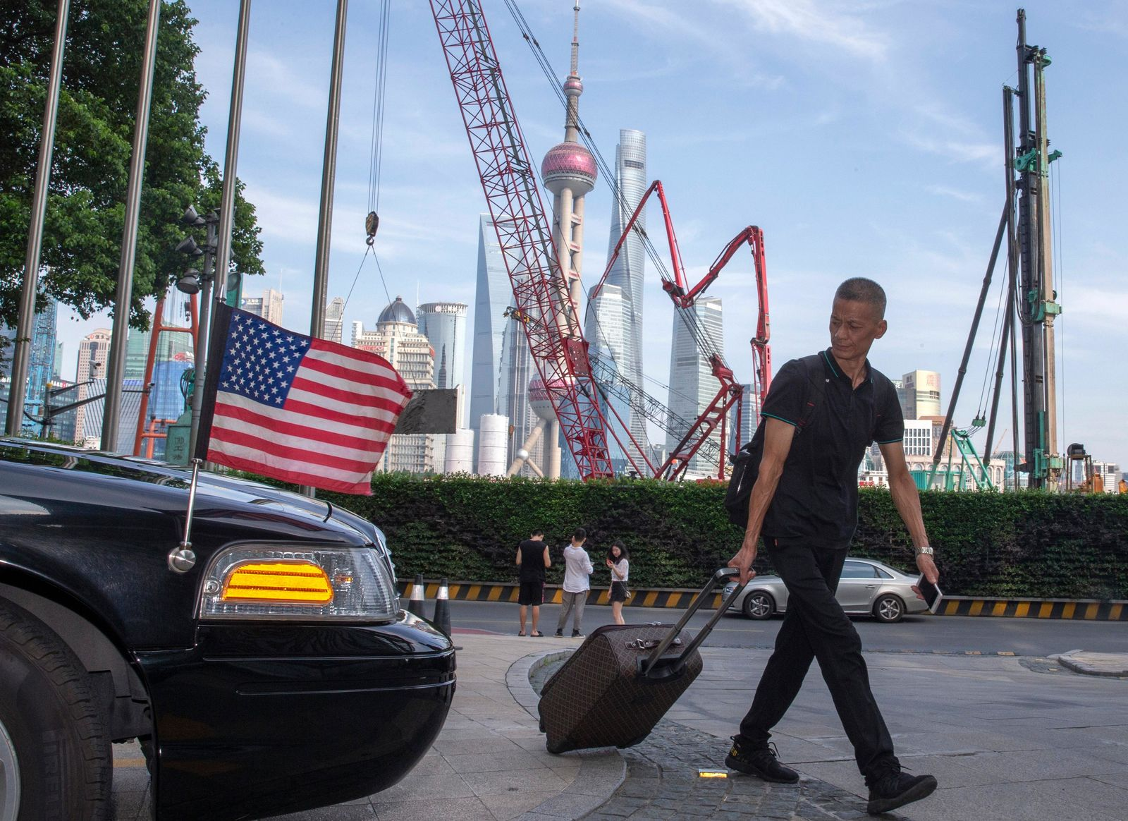 FILE - In this July 30, 2019, file photo, a traveller pulls a trolley past a U.S. embassy car outside a hotel in Shanghai. (AP Photo/Ng Han Guan, File)