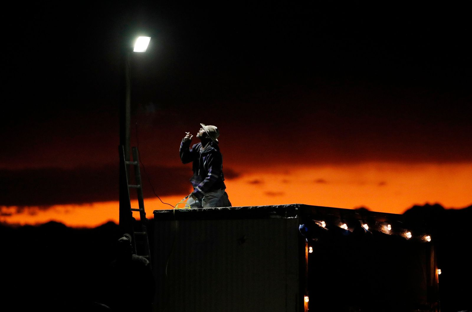 "A man sets up a a light in preparation for an event inspired by the ""Storm Area 51"" internet hoax near the Little A'Le'Inn motel and cafe, Thursday, Sept. 19, 2019, in Rachel, Nev. Hundreds have arrived in the desert after a Facebook post inviting people to ""see them aliens"" got widespread attention and gave rise to festivals this week. (AP Photo/John Locher)"
