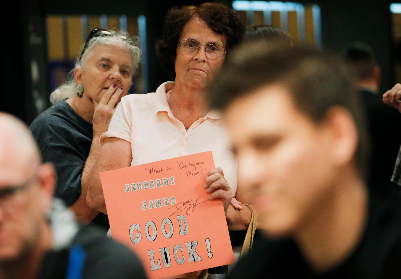 """Jeopardy!"" fans Judi Blomquist, holding sign, and Susan Youngblood watch as ""Jeopardy!"" champion and professional sports gambler James Holzhauer, right, plays in a tournament at the World Series of Poker, Monday, June 24, 2019, in Las Vegas. (AP Photo/John Locher)"