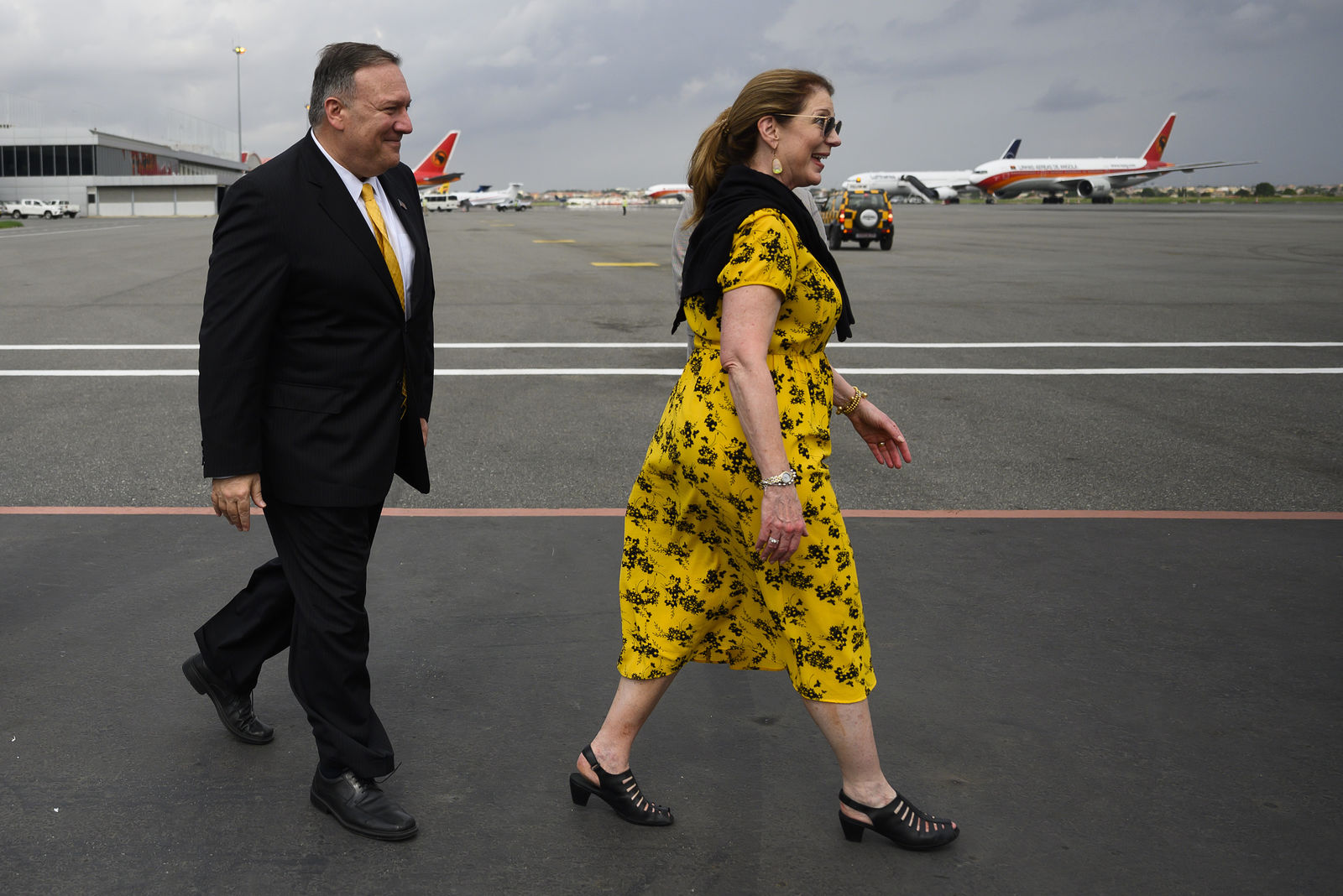 US Secretary of State, Mike Pompeo, right, and his wife, Susan Pompeo walk on the tarmac before leaving Angola at the Luanda International Airport in Luanda, Angola, Monday Feb. 17, 2020. (Andrew Caballero-Reynolds/Pool via AP)