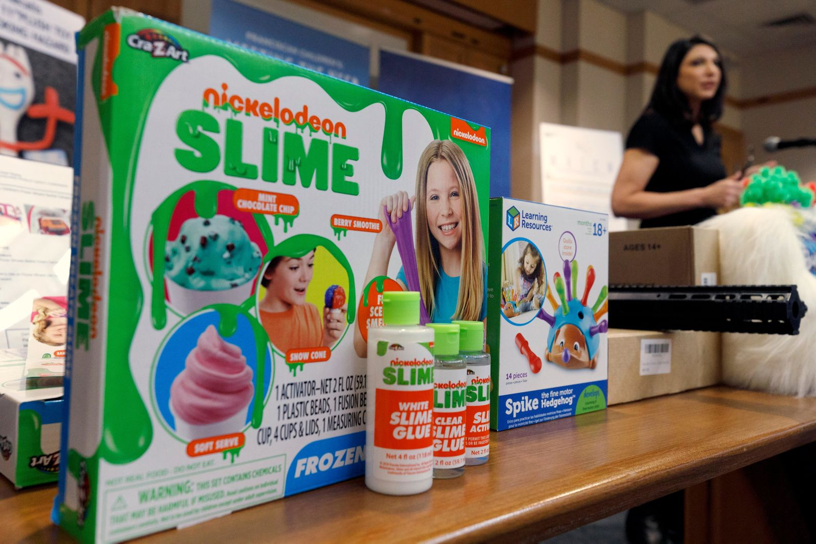 Joan Siff, president of World Against Toys Causing Harm, speaks behind an array of toys, including ice cream-scented Nickelodeon slime, during a news conference in Boston, Tuesday, Nov. 19, 2019. The organization notes that Nickelodeon's Frozen Treats Slime includes mint chocolate chip, berry smoothie, and snow cone-scented versions of the goo even as it warns the products are made of harmful chemicals and shouldn't be eaten. (AP Photo/Michael Dwyer)