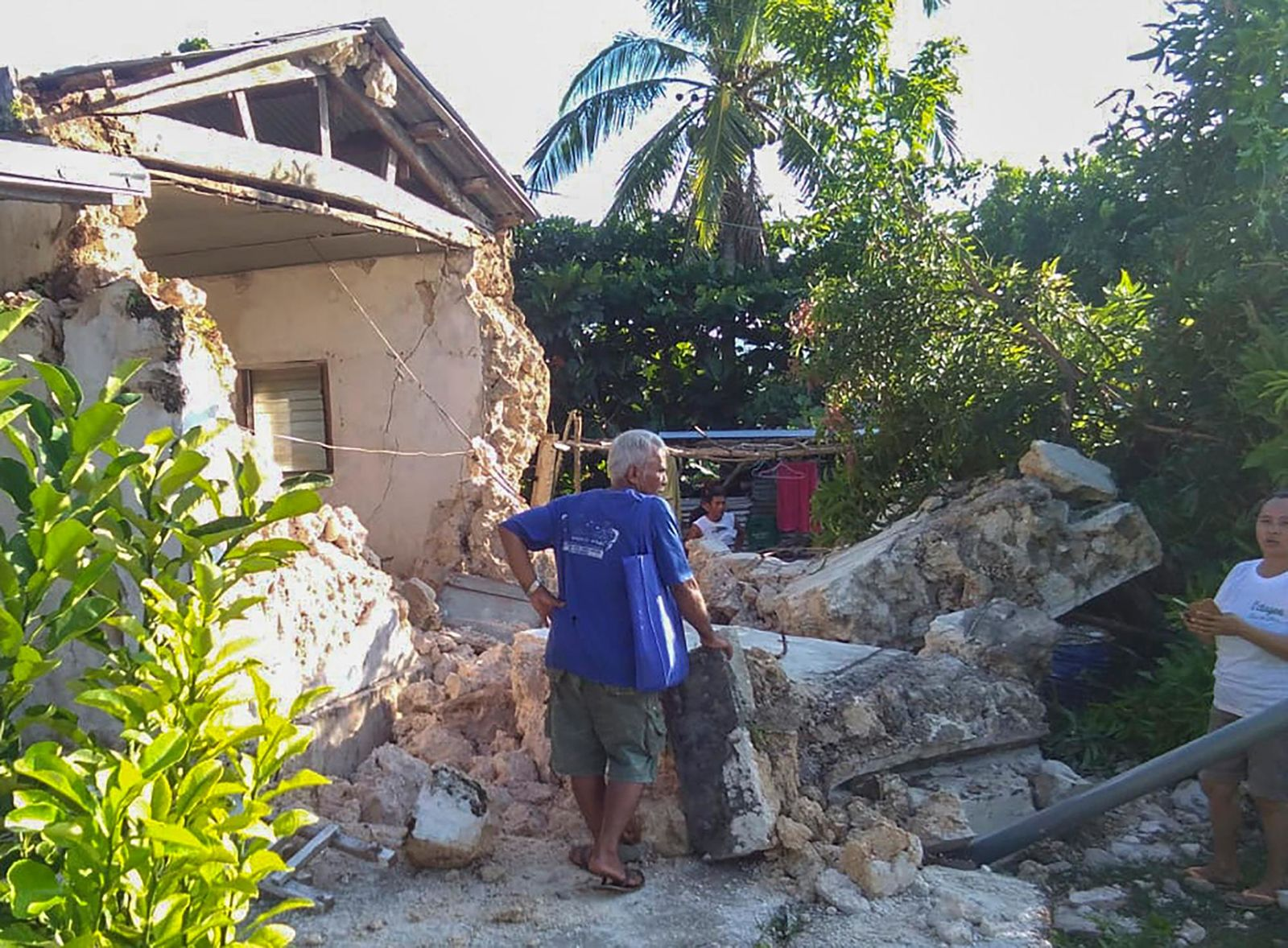 A resident looks at damaged houses in Itbayat town, Batanes islands, northern Philippines on Saturday, July 27, 2019. Two strong earthquakes hours apart struck a group of sparsely populated islands in the Luzon Strait in the northern Philippines early Saturday. (AP Photo/Agnes Salengua Nico)