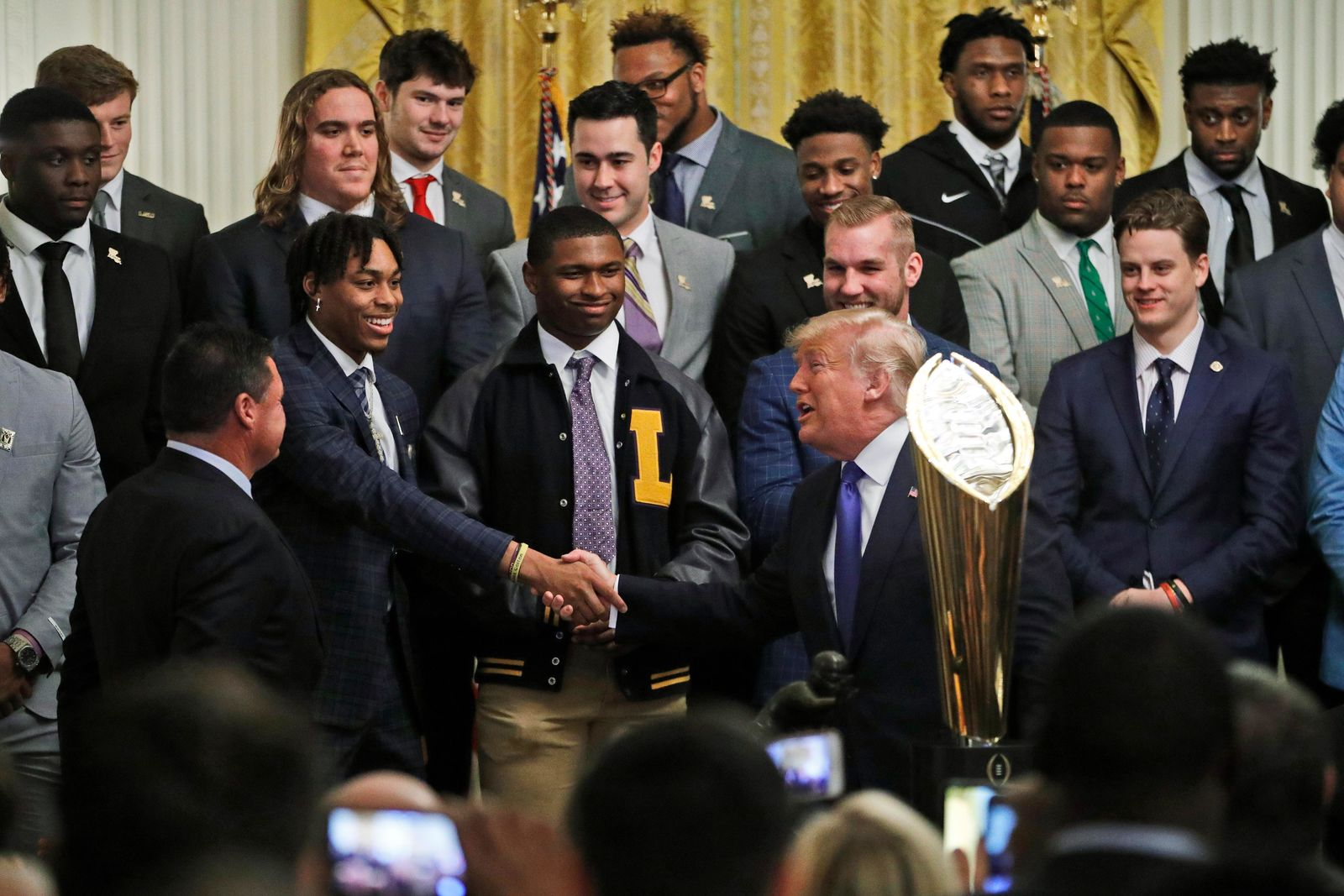 President Donald Trump, right, shakes the hand of LSU wide receiver Justin Jefferson, as he honors the members of the Louisiana State University NCAA college championship football team in the East Room at the White House, Friday, Jan. 17, 2020, in Washington. (AP Photo/Steve Helber)