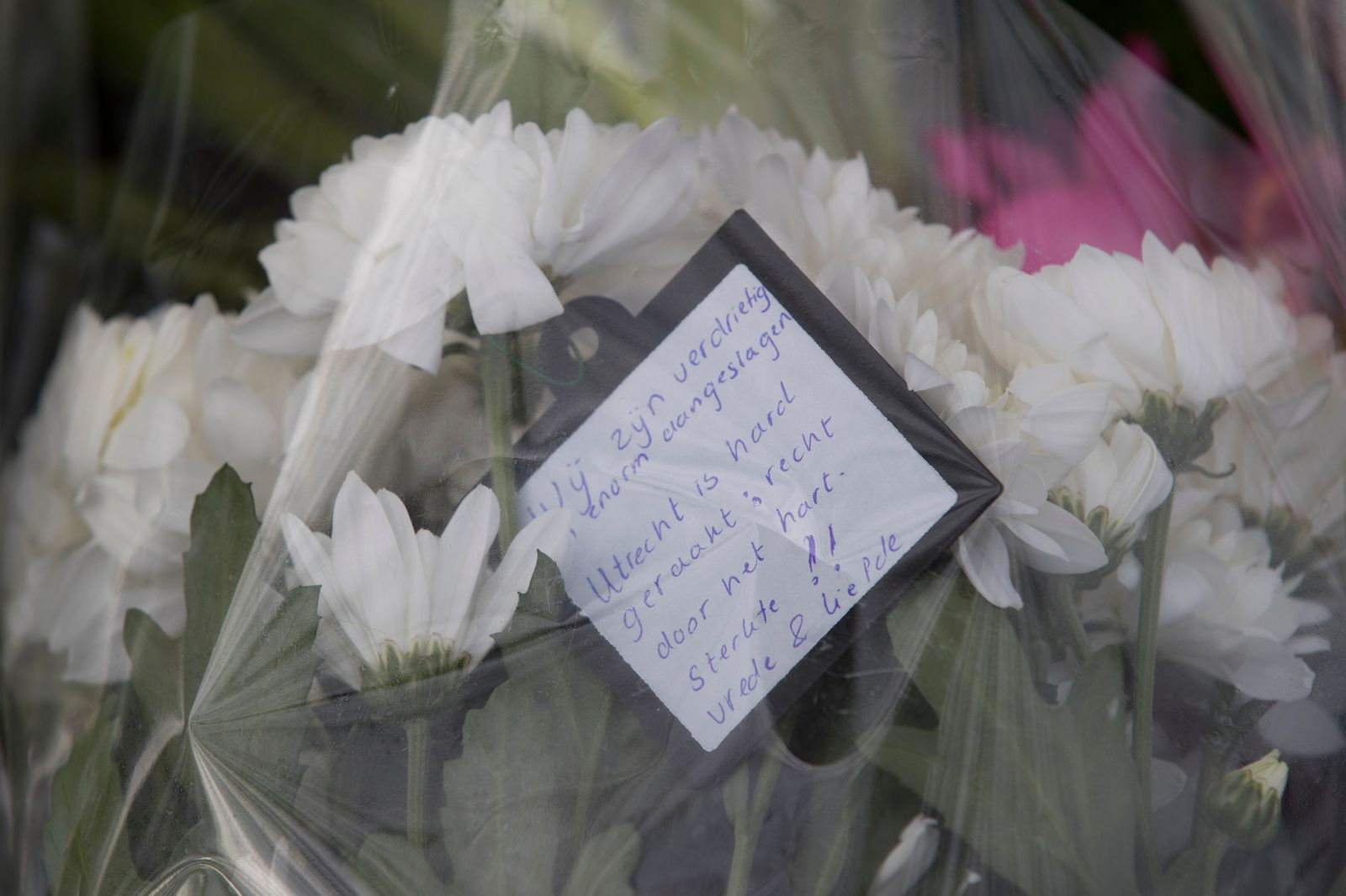 "A text reads ""We are sad and deeply shaken, Utrecht has been hit hard; straight through the heart. Strength !! Peace and Love."" attached to a bouquet of flowers near the site of a shooting incident in a tram in Utrecht, Netherlands, Tuesday, March 19, 2019. (AP Photo/Peter Dejong)"