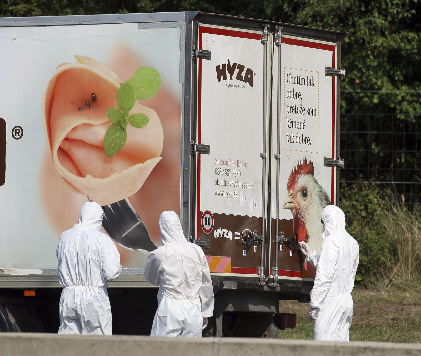 FILE - In this Thursday, Aug. 27, 2015 file photo, investigators stand near an abandoned truck on the shoulder of Highway A4 near Parndorf, Austria, south of Vienna. (AP Photo/Ronald Zak, file)