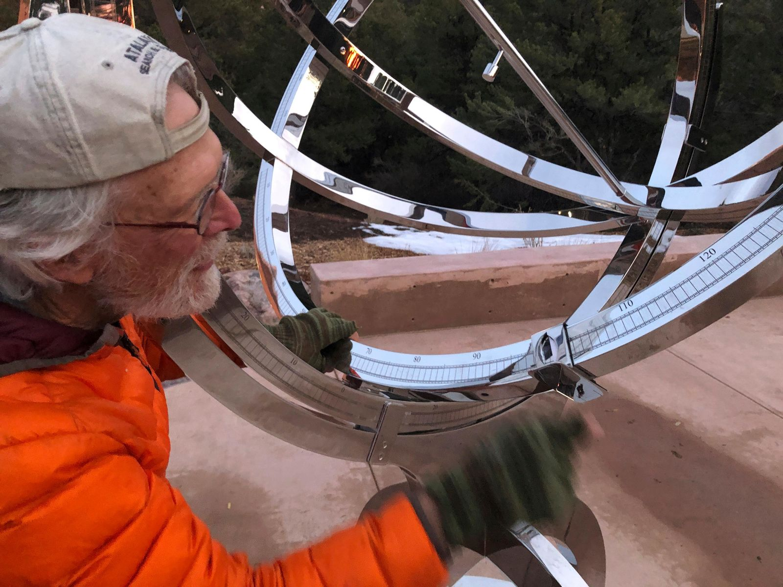 In this Dec. 11, 2019 photo Bill Donahue, a retired teacher and director of laboratories at St. John's College, adjusts the site on an armillary sphere to track planetary rotations and explore the history of astronomy in Santa Fe, N.M. The unique precision-steel replica of an instrument created by Danish astonomer Tycho Brahe was commissioned by graduates of the college where students trace the evolution of math and science from early civilizations. (AP Photo/Morgan Lee)