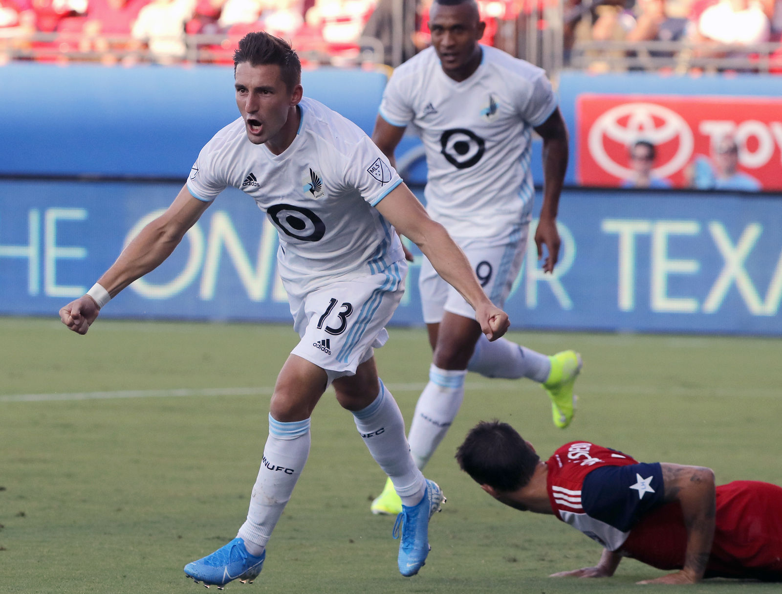 FILE - In this Aug. 10, 2019, file photo, Minnesota United's Ethan Finlay (13) and Angelo Rodriguez, rear left, celebrate Finlay's goal against FC Dallas in the first half of an MLS soccer match in Frisco, Texas. (AP Photo/Tony Gutierrez, File)
