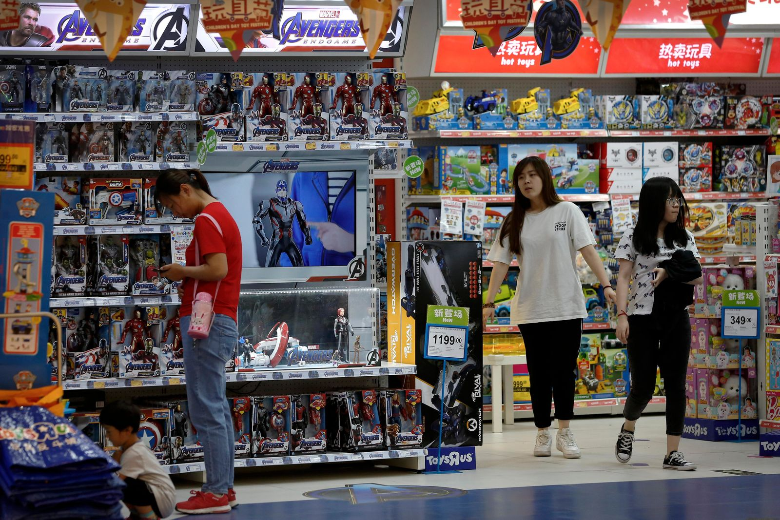 Customers shop near a section selling Marvel Avengers toys by American toymaker Hasbro at a toy store in Beijing, Thursday, May 23, 2019. An escalating trade war between the U.S. and China could mean higher prices on a broad array of products from toys to clothing. But some retailers will be less equipped to handle the pain than others, leaving consumers to carry the load. (AP Photo/Andy Wong)